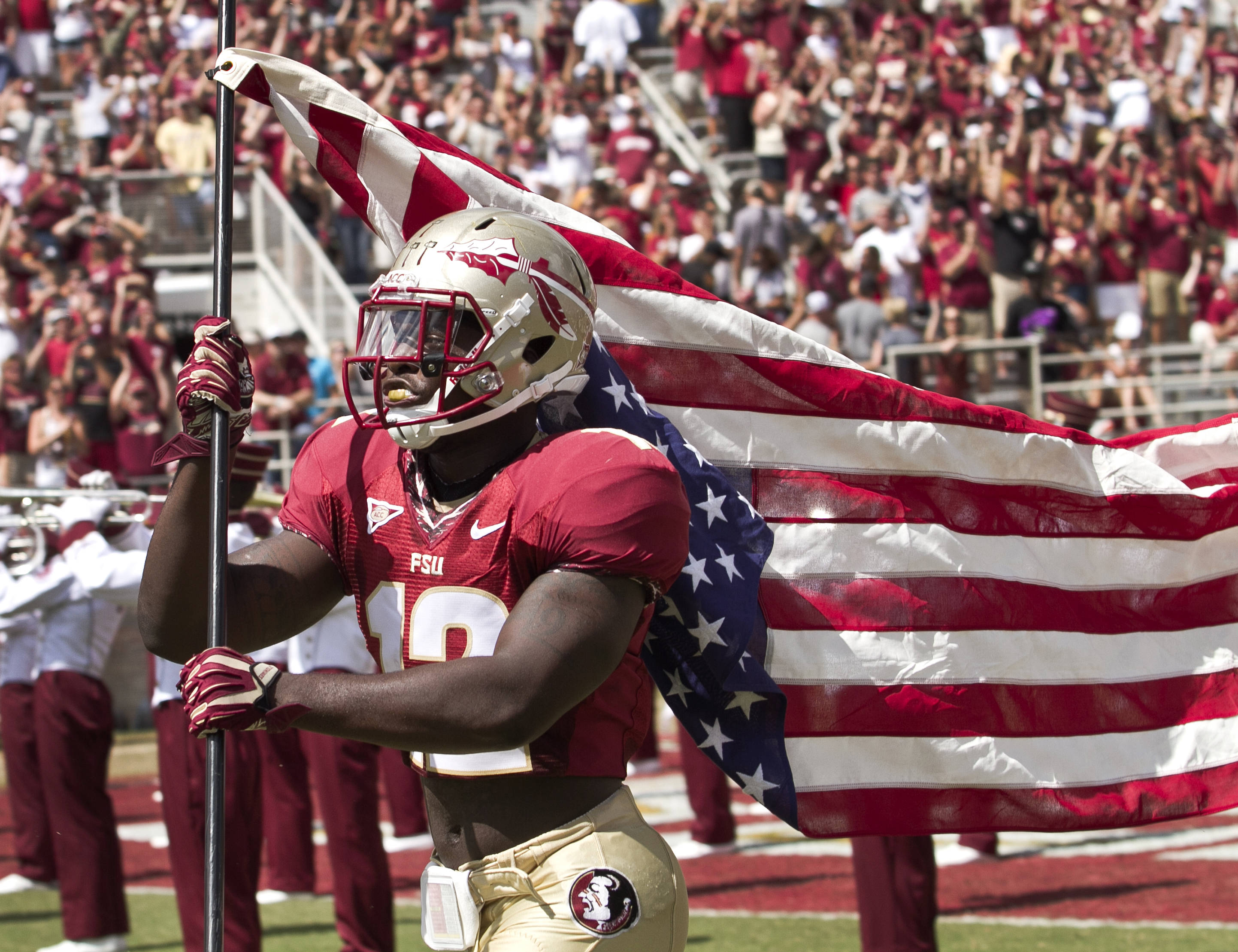 Reggie Northrup (12) carrying the flag leading FSU out on the field for military appreciation day, FSU vs Wake Forest, 9/15/12 (Photo by Steve Musco)