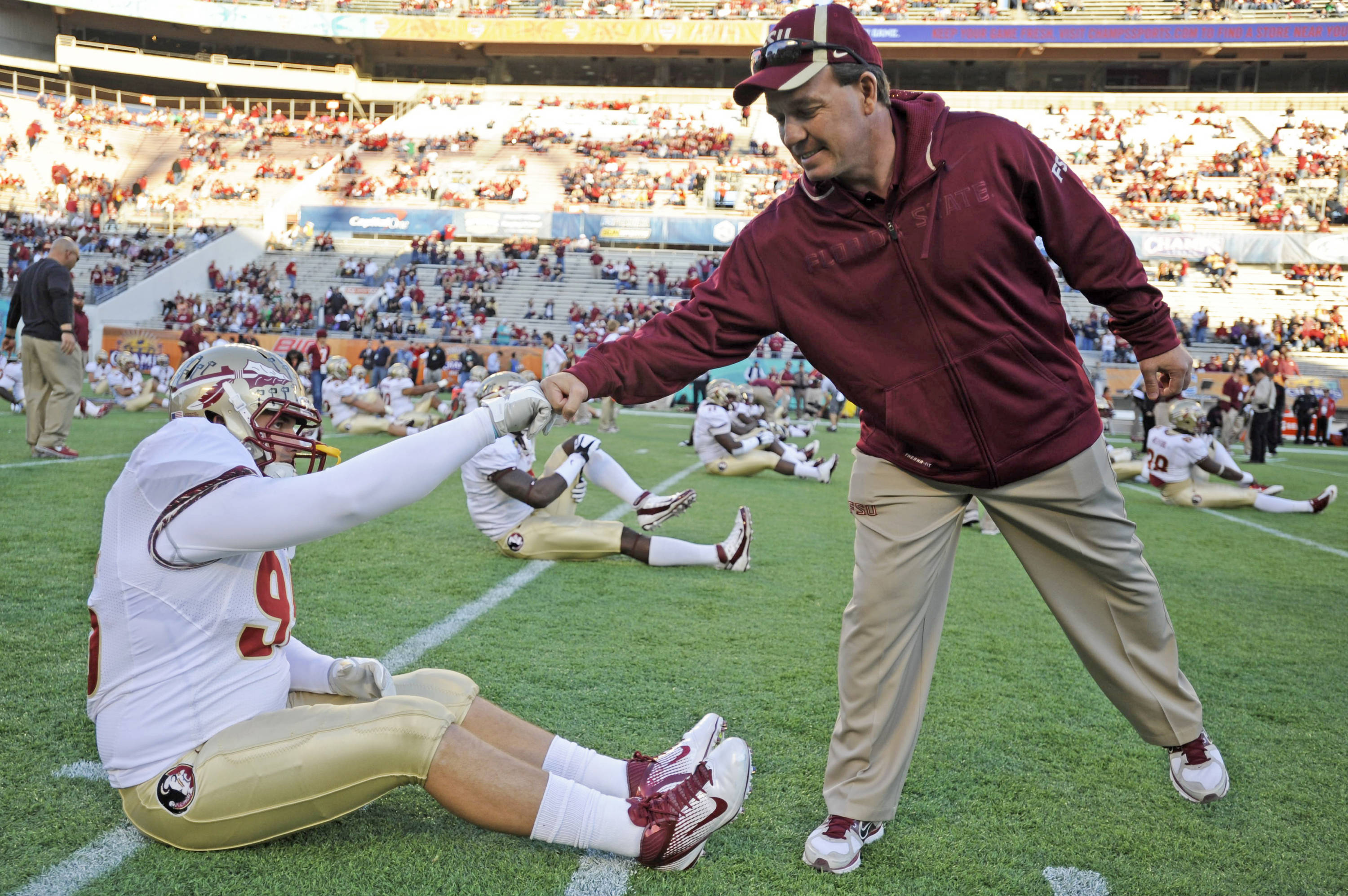 Jimbo Fisher and Bjoern Werner (95) meet during warmups before the Champs Sports Bowl.  Werner was one of the most feared defensive ends in the nation in 2011, and is poised for big things in 2012