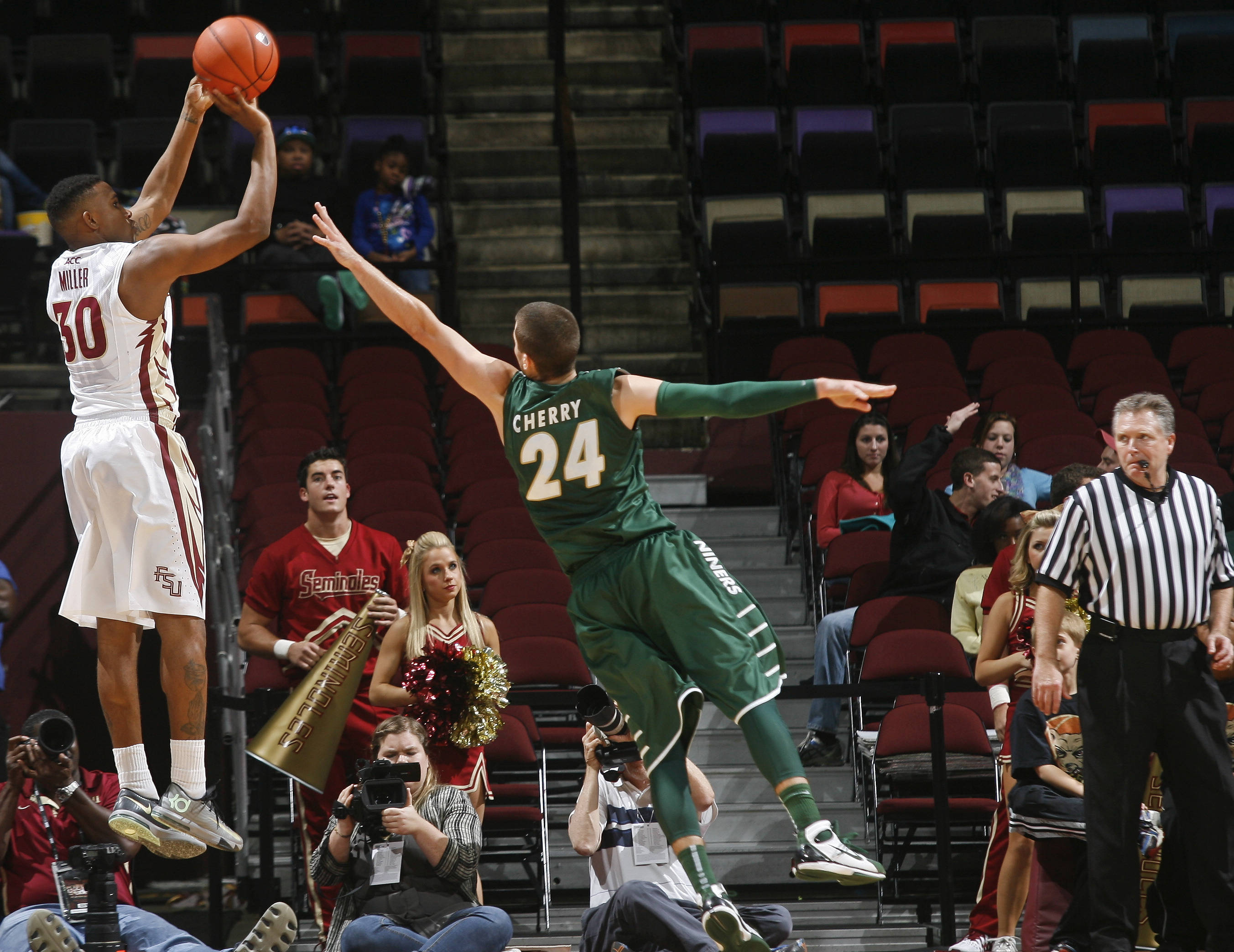 Dec 17, 2013; Tallahassee, FL, USA; Florida State Seminoles guard Ian Miller (30) makes a three-point basket over the defense of Charlotte 49ers guard Ben Cherry (24) in the second half of their game at the Donald L. Tucker Center. The Florida State Seminoles beat the Charlotte 49ers 106-62. Mandatory Credit: Phil Sears-USA TODAY Sports