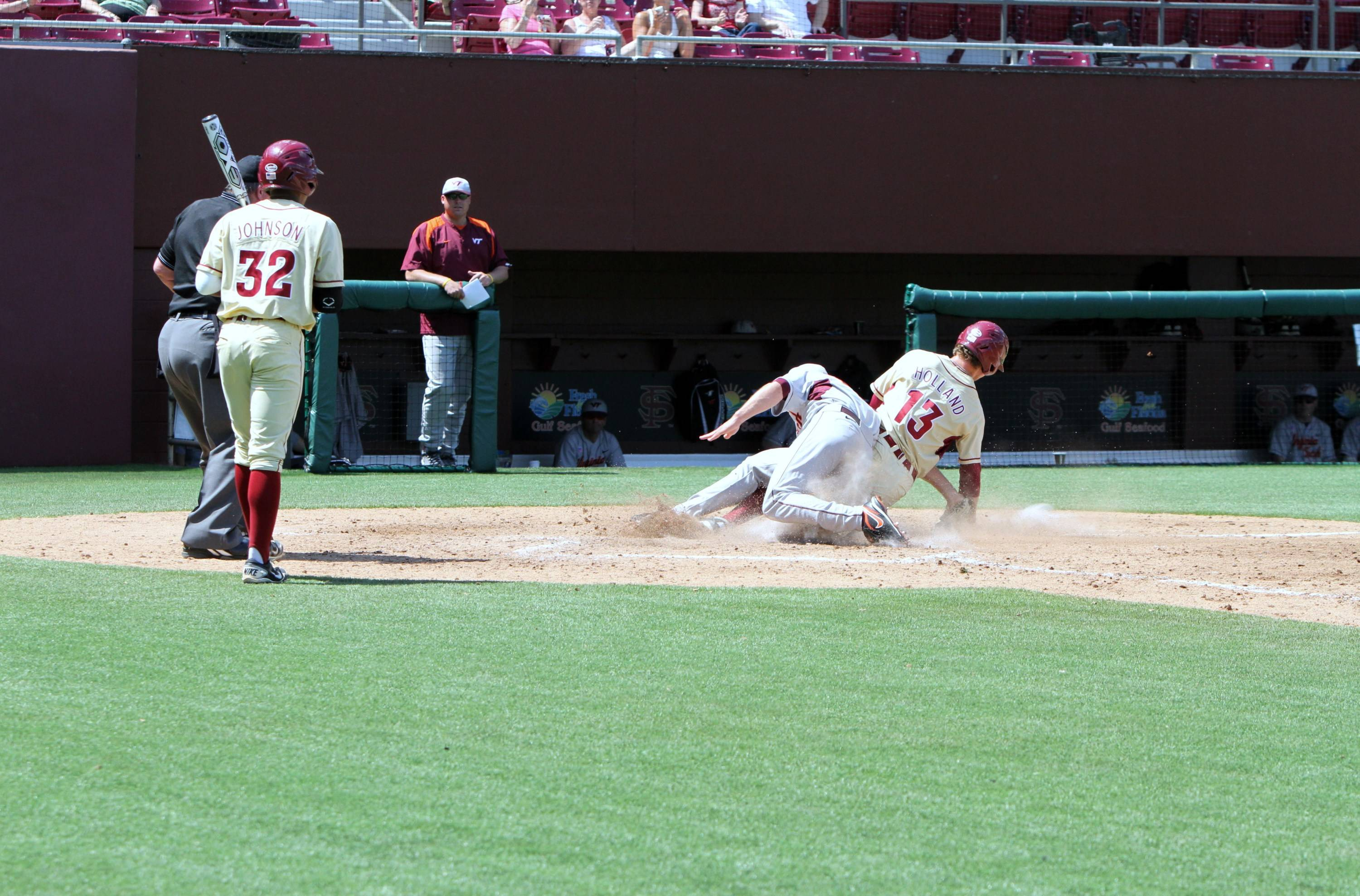John Holland slides in just in front of the tag at home for FSU's 11th run of the afternoon.