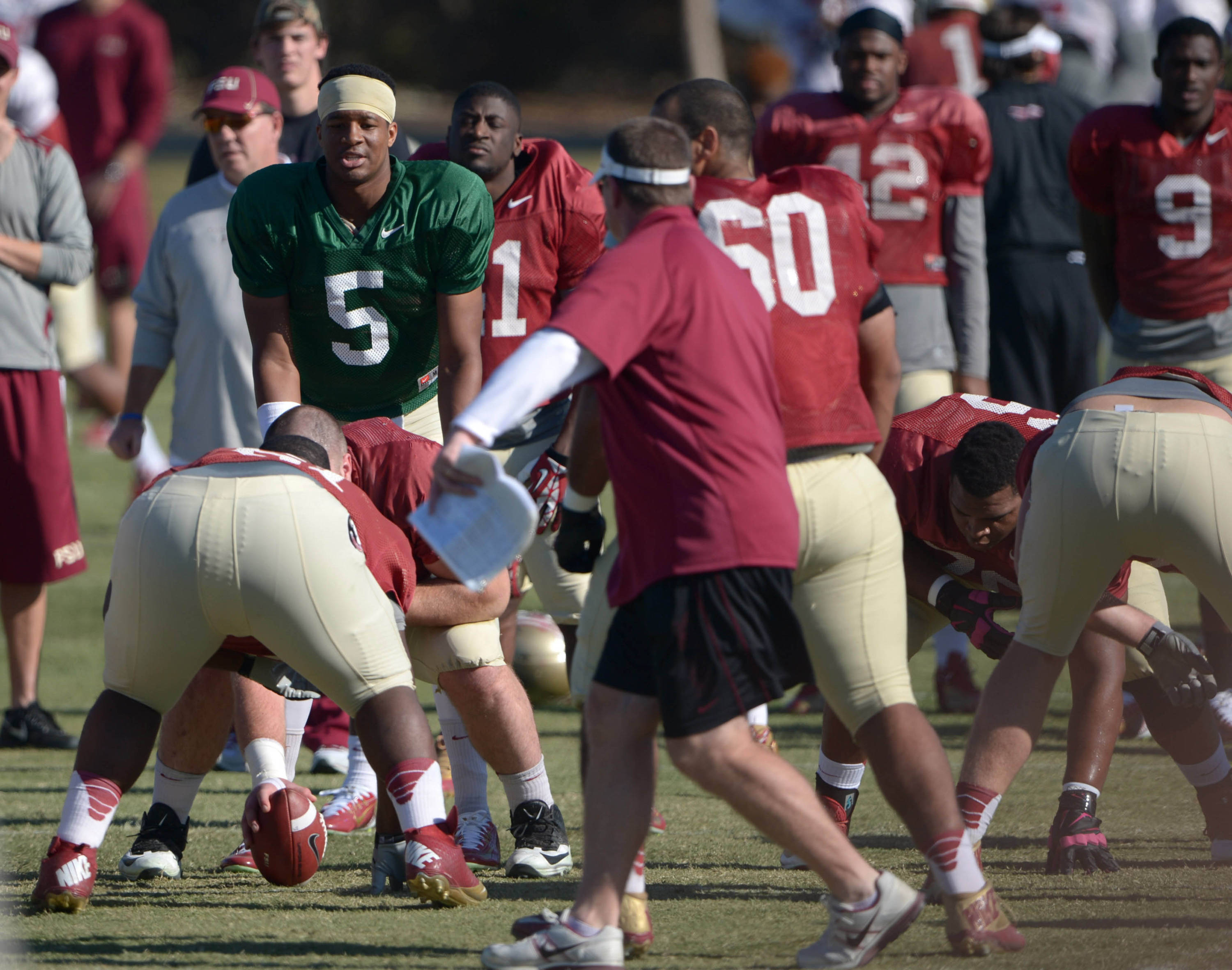 Florida State Seminoles quarterback Jameis Winston (5) takes the snap under the supervision of quarterbacks coach Randy Sanders at practice for the 2014 BCS National Championship at the Jack R. Hammett Sports Complex. Mandatory Credit: Kirby Lee-USA TODAY Sports