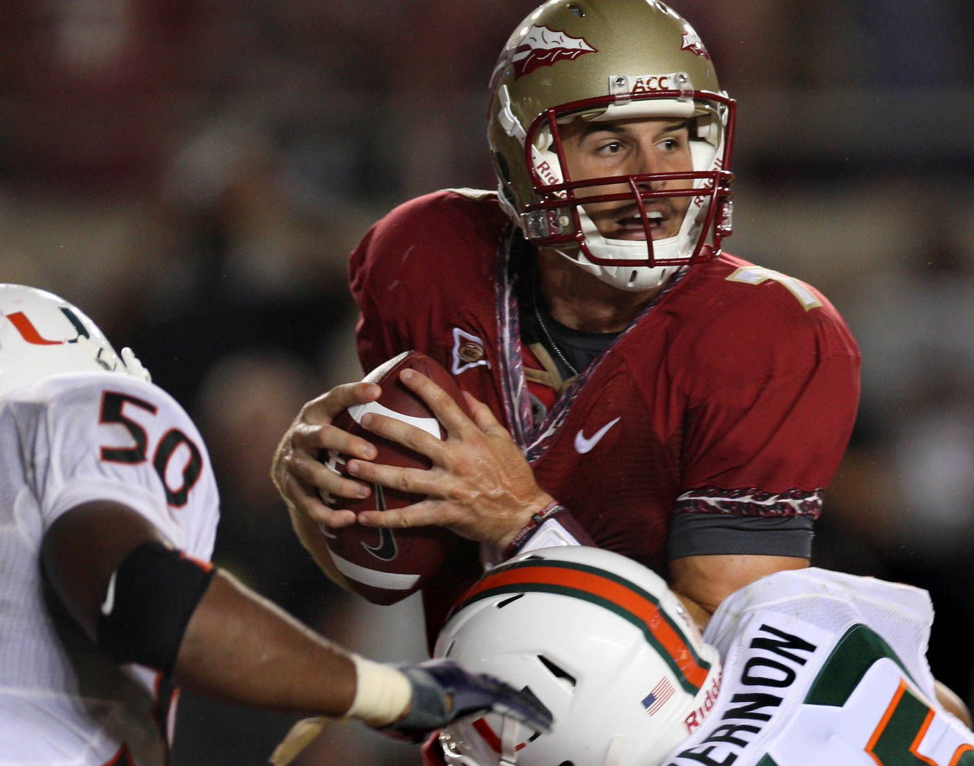 Florida State quarterback Christian Ponder, center, is stopped late in the fourth quarter by Miami linebacker Darryl Sharpton, left, and defensive lineman Olivier Vernon during an NCAA college football game Monday, Sept. 7, 2009, in Tallahassee, Fla. Miami won 38-34.(AP Photo/Phil Coale)