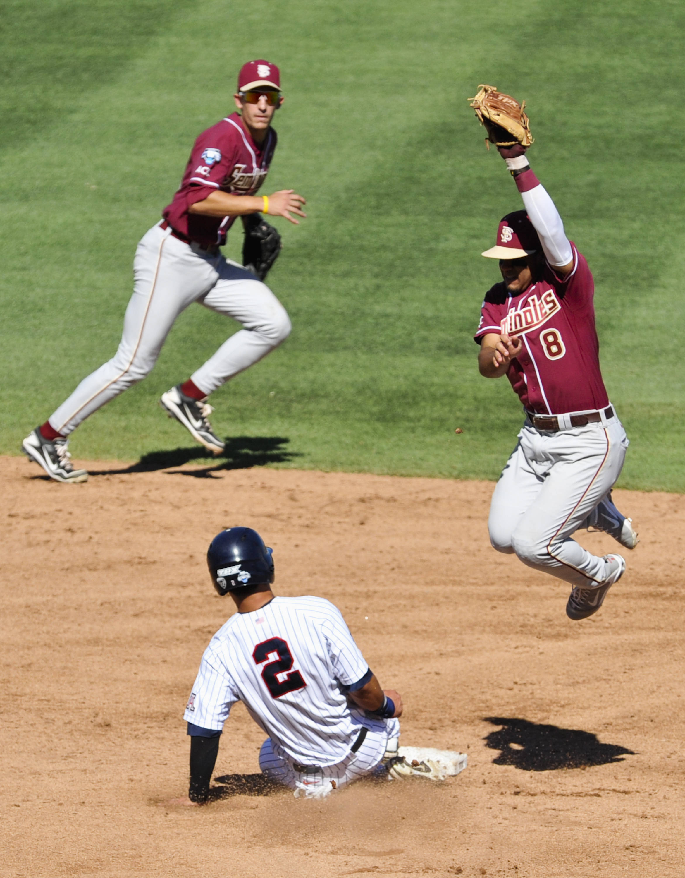 Arizona's Robert Refsnyder (2) steals second base as Florida State second baseman Devon Travis leaps for the ball, and shortstop Justin Gonzalez runs by. (AP Photo/Dave Weaver)