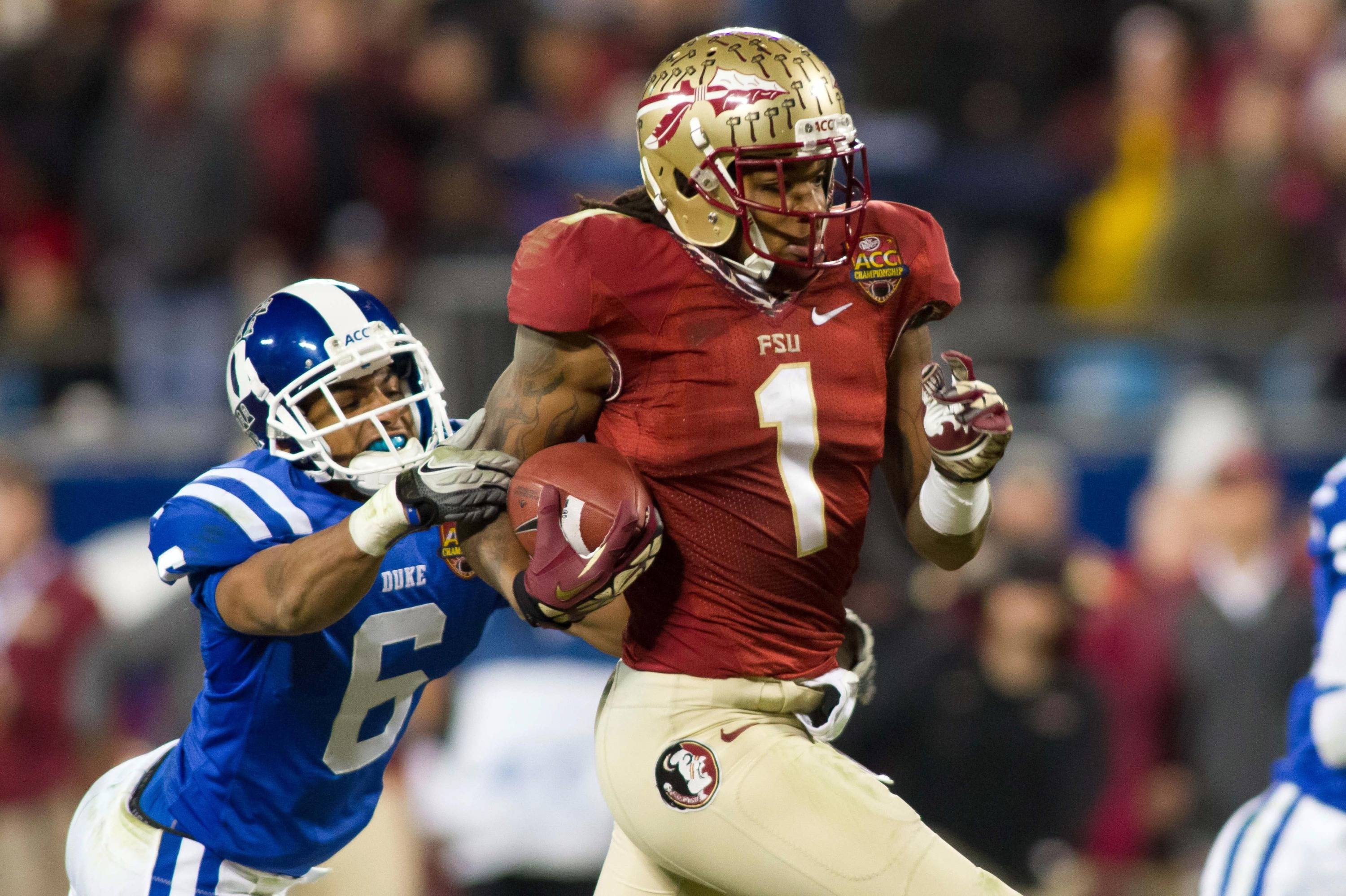 Dec 7, 2013; Charlotte, NC, USA; Florida State Seminoles wide receiver Kelvin Benjamin (1) runs by the tackle of Duke Blue Devils cornerback Ross Cockrell (6) during the third quarter at Bank of America Stadium. FSU defeated Duke 45-7. Mandatory Credit: Jeremy Brevard-USA TODAY Sports