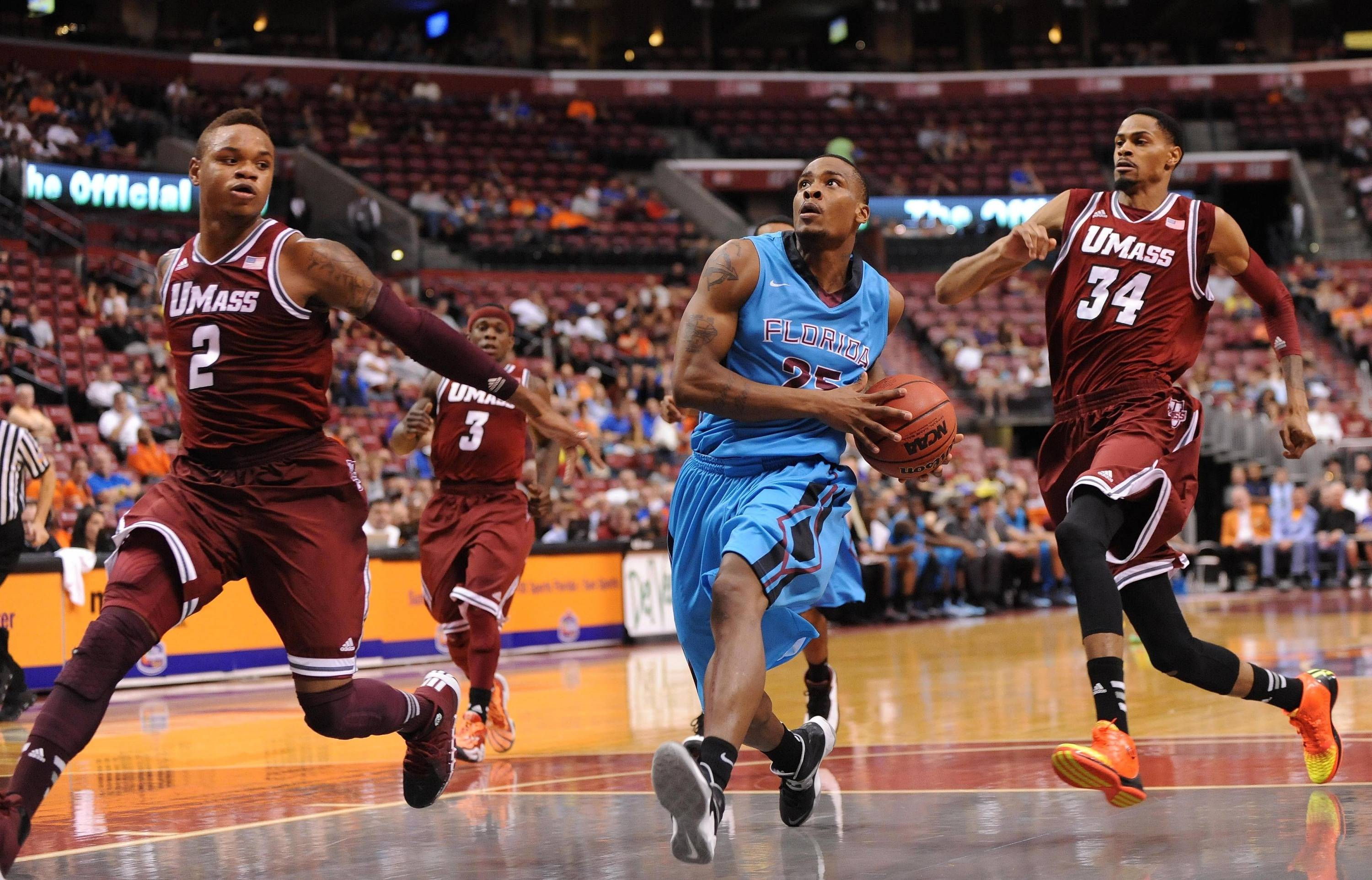 Dec 21, 2013; Sunrise, FL, USA; Florida State Seminoles guard Aaron Thomas (center) drives to the basket as Massachusetts Minutemen guard Derrick Gordon (left) and forward Raphiael Putney (right) defend during the first half at BB&T Center. Mandatory Credit: Steve Mitchell-USA TODAY Sports
