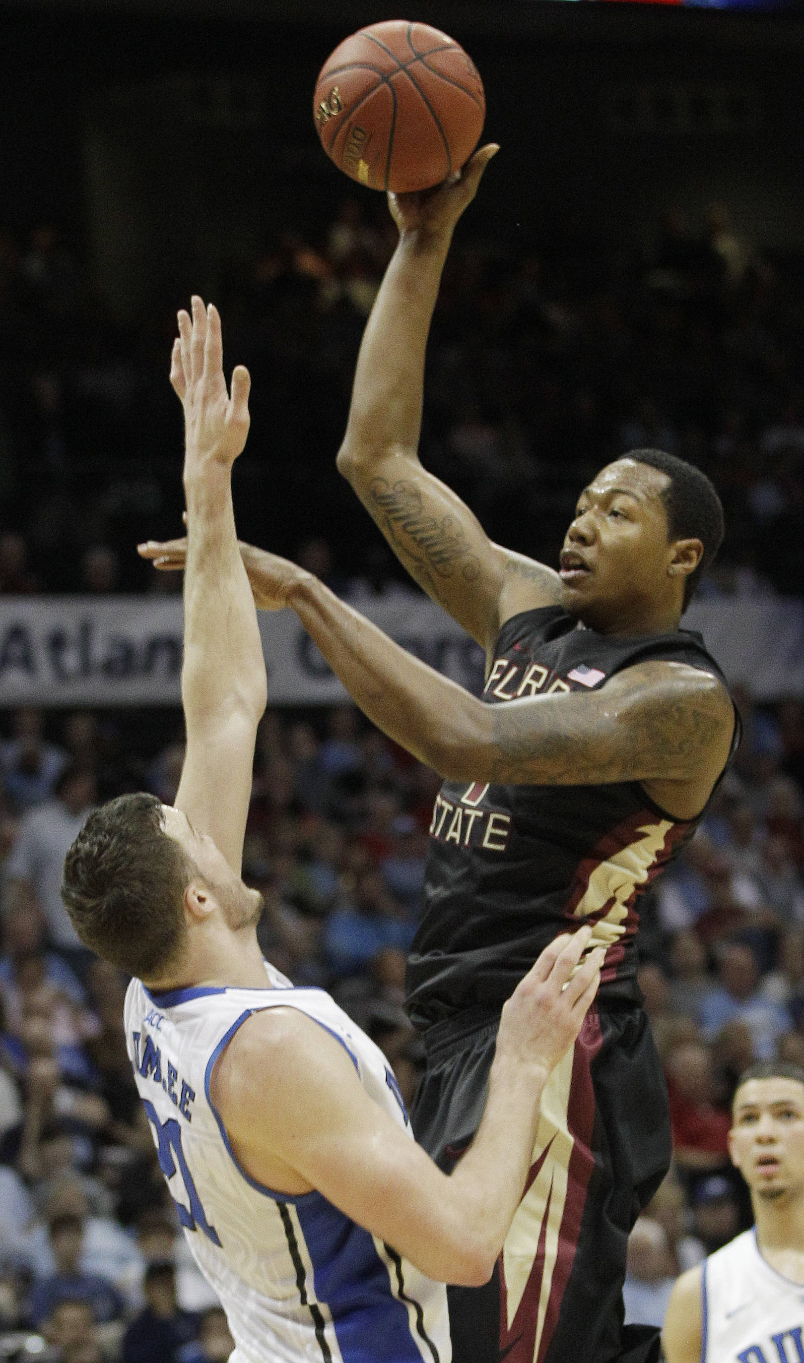 Florida State forward/center Xavier Gibson (1) shoots over Duke forward Miles Plumlee (21) during the first half of an NCAA college basketball game in the semifinals of the Atlantic Coast Conference tournament, Saturday, March 10, 2012, in Atlanta. (AP Photo/Chuck Burton)