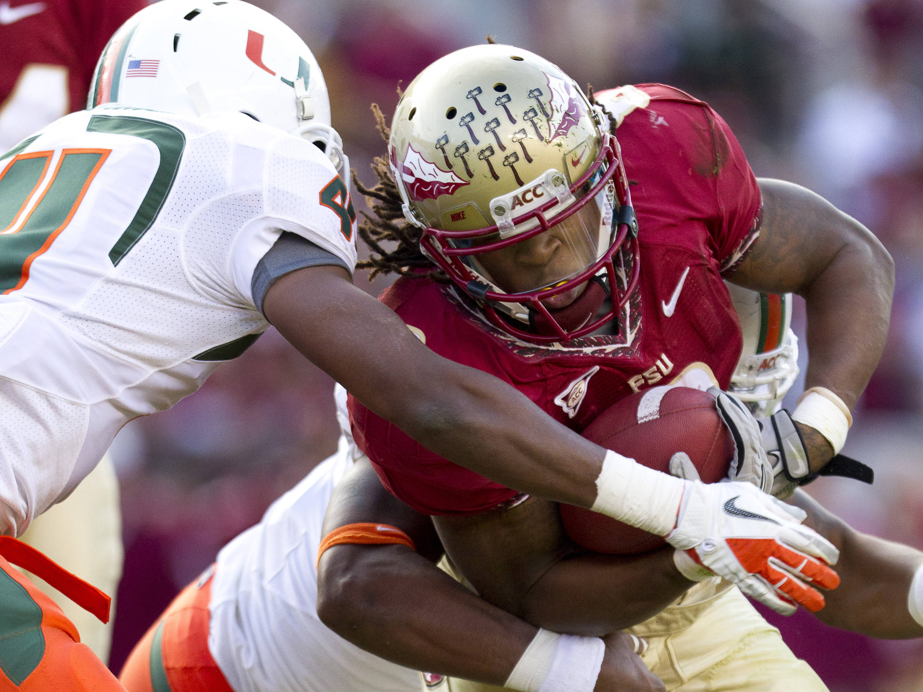 Devonta Freeman (8) prevents a Miami player from stripping the ball during the football game against Miami on November 12, 2011.