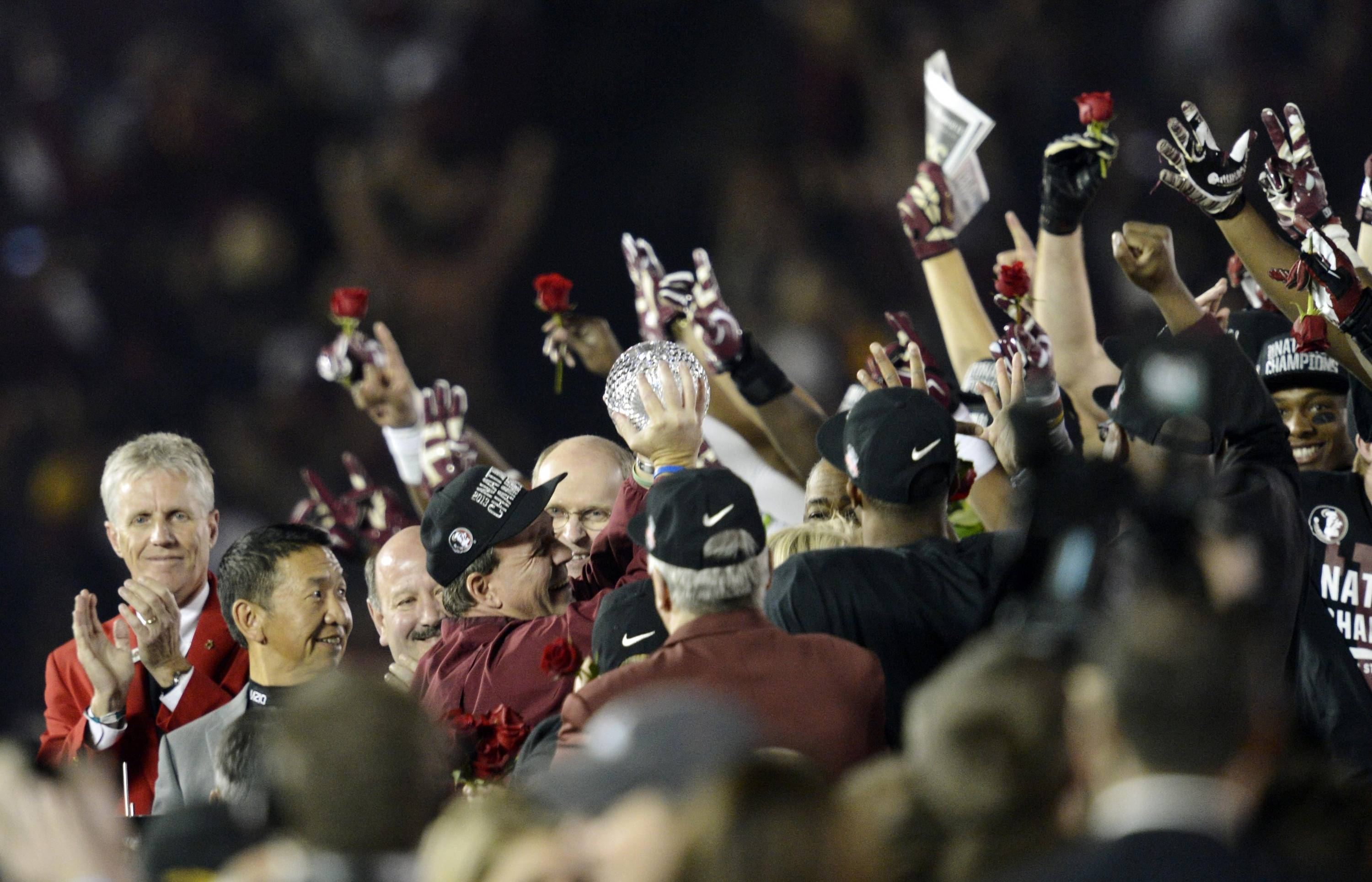 Jan 6, 2014; Pasadena, CA, USA; Florida State Seminoles head coach Jimbo Fisher shows off the Coaches Trophy to his team after the 2014 BCS National Championship game against the Auburn Tigers at the Rose Bowl.  Mandatory Credit: Robert Hanashiro-USA TODAY Sports