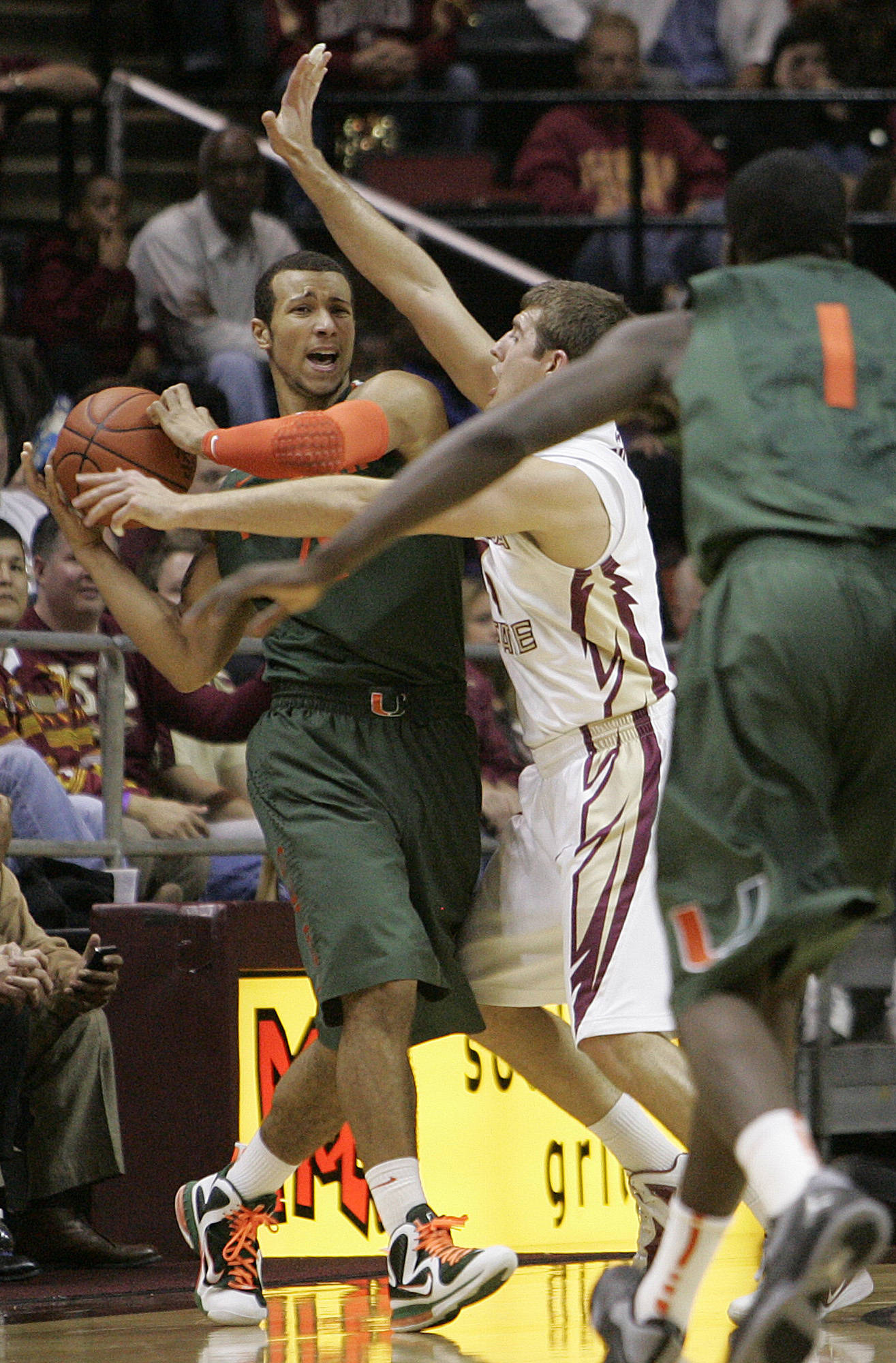 Miami's Trey McKinney Jones looks for help from his teammates as he backed up by the defense of Florida State's Luke Loucks  in the second half of an NCAA college basketball game. Florida State won 64-59 on Saturday, Feb. 11, 2012 in Tallahassee, Fla.(AP Photo/Steve Cannon)