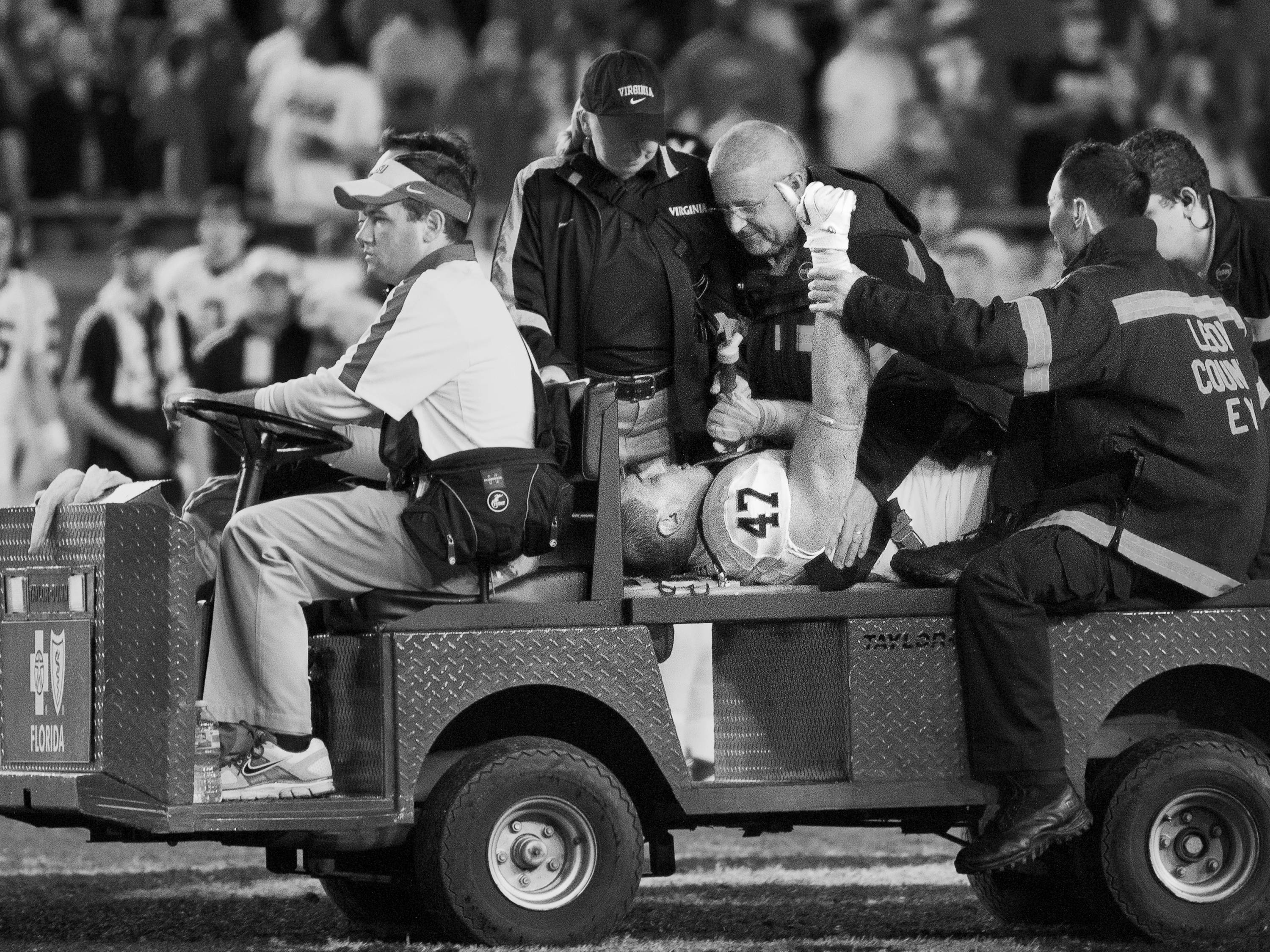 An EMT helps Virginia's Bill Schautz give the crowd a thumbs up as he leaves the field on a cart during the football game against Virginia on November 29, 2011.