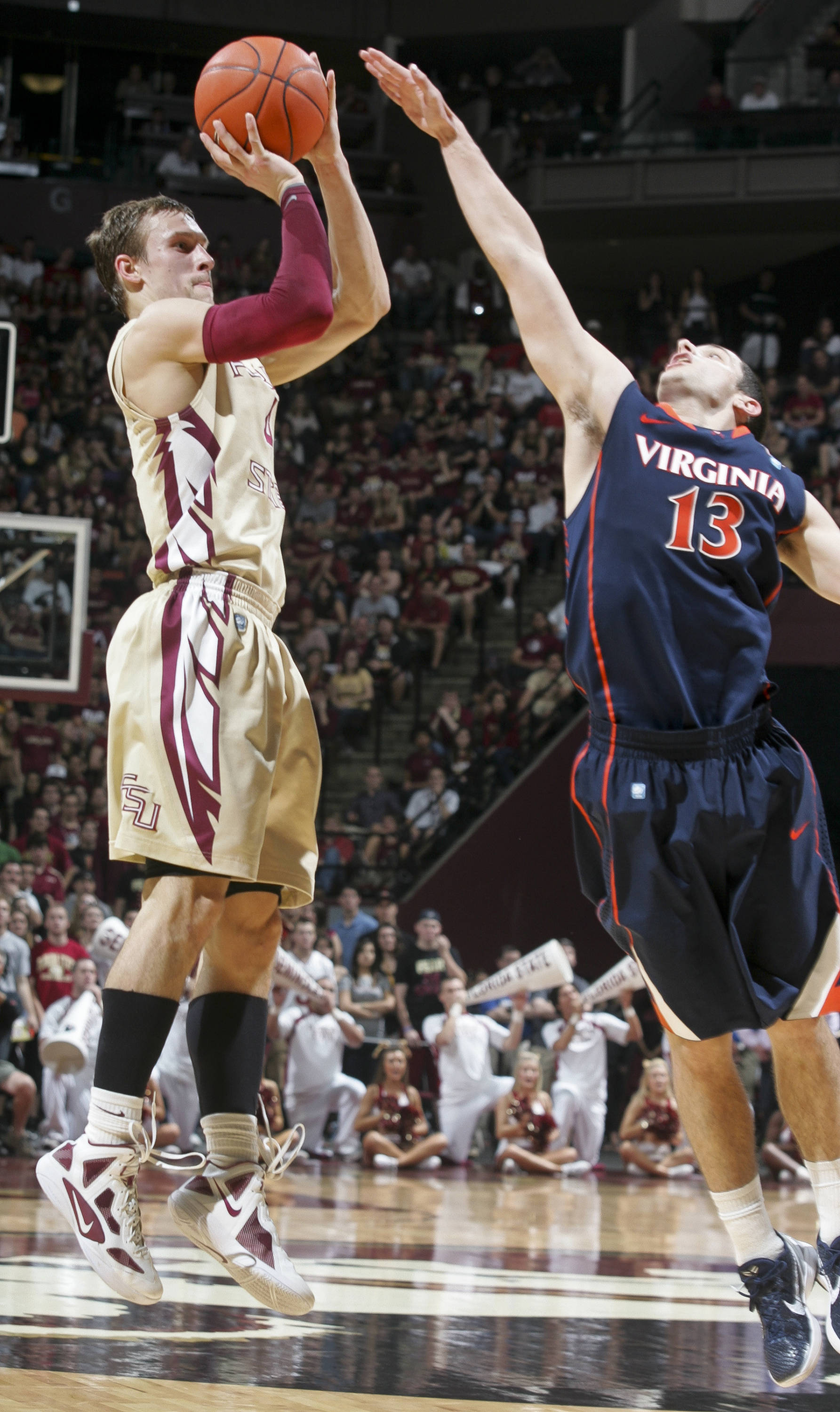 Florida State's Deividas Dulkys (4) makes a basket over the defense of Virginia's Sammy Zeglinski (13) in the first half of an NCAA college basketball game on Saturday, Feb. 4, 2012, in Tallahassee, Fla. Florida State won 58-55. (AP Photo/Phil Sears)