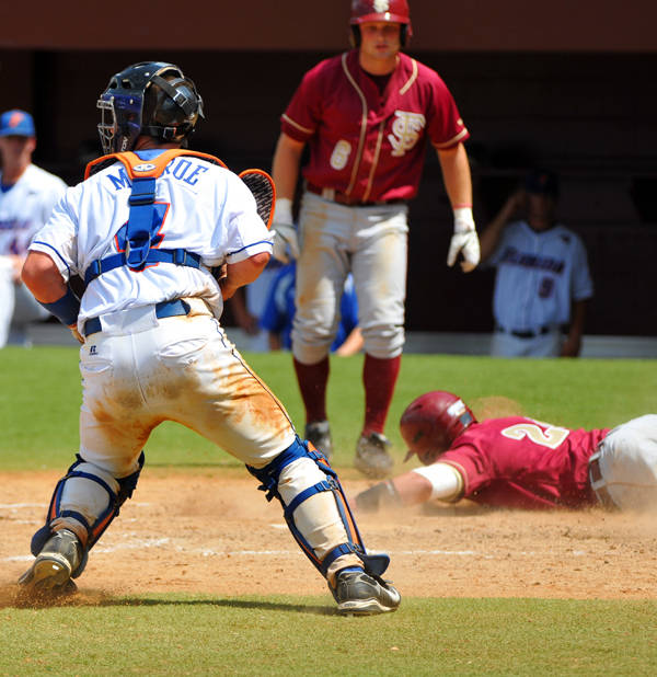 Dennis Guinn slides in safely on a play at the plate