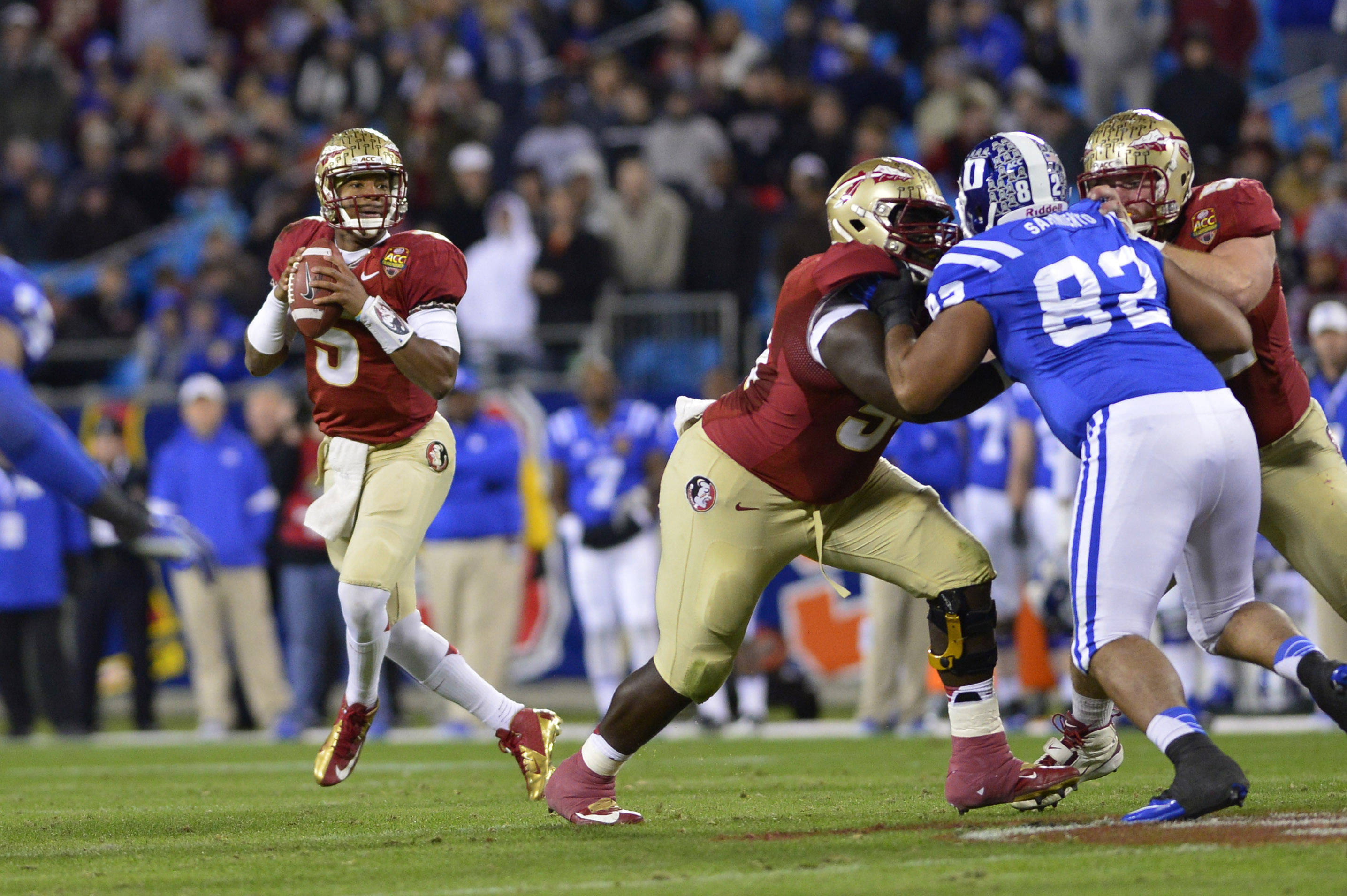 Dec 7, 2013; Charlotte, NC, USA; Florida State Seminoles quarterback Jameis Winston (5) looks to pass Duke Blue Devils defensive tackle Sydney Sarmiento (82) defends in the second quarter at Bank of America Stadium. Mandatory Credit: Bob Donnan-USA TODAY Sports