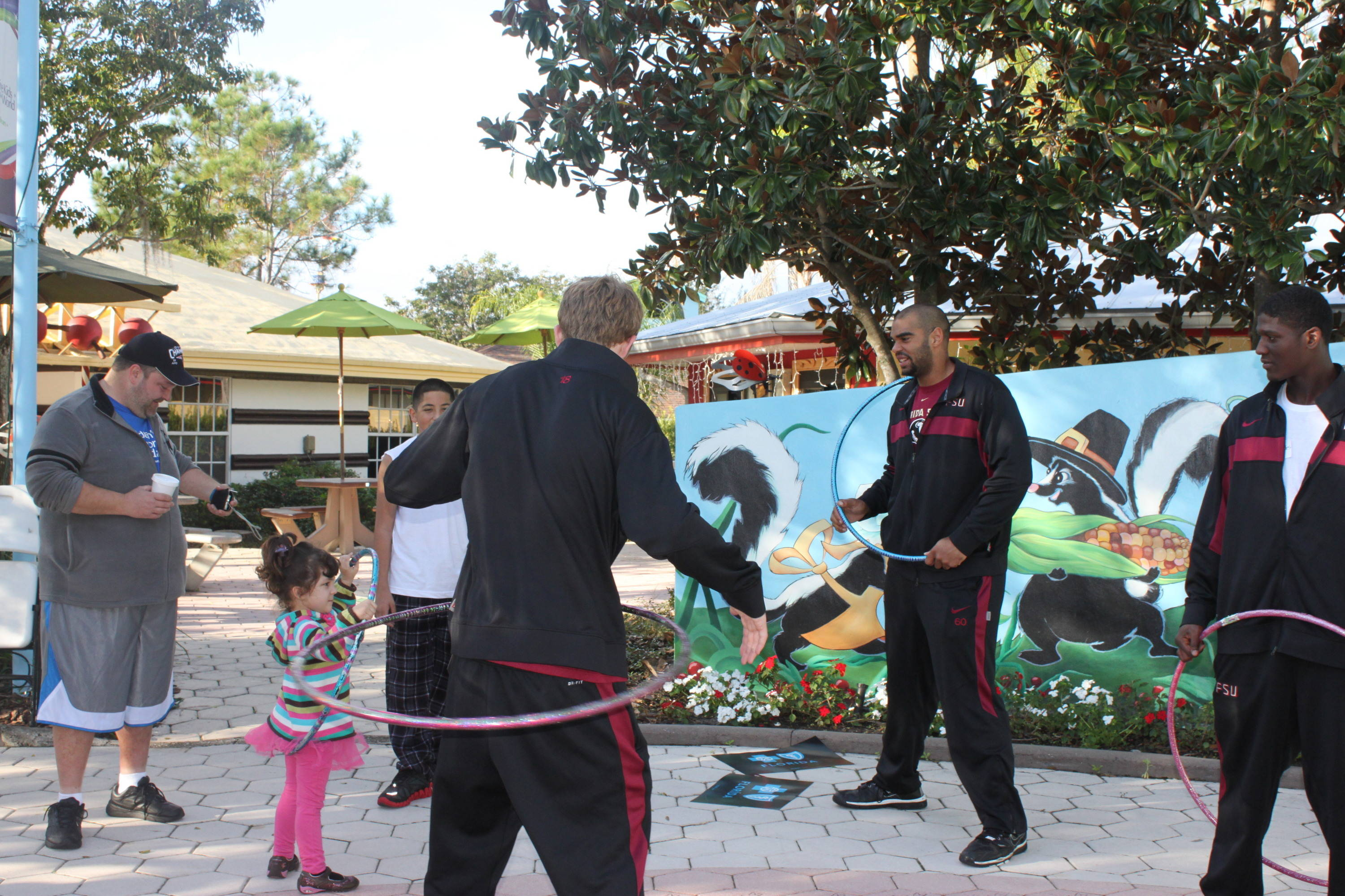 One young girl gets some pointers on the fine art of the Hoola Hoop from a group of 'Noles.
