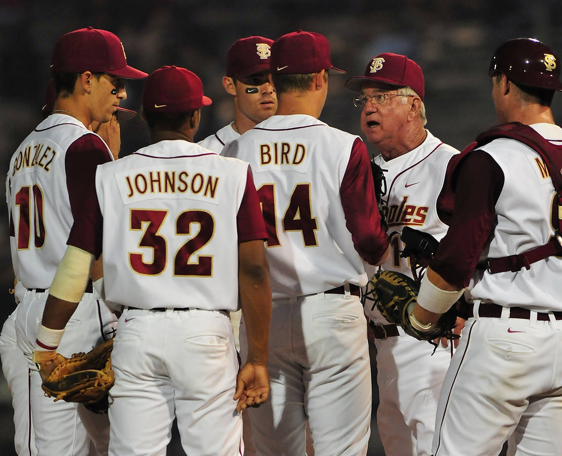 Head coach Mike Martin has a meeting at the mound.
