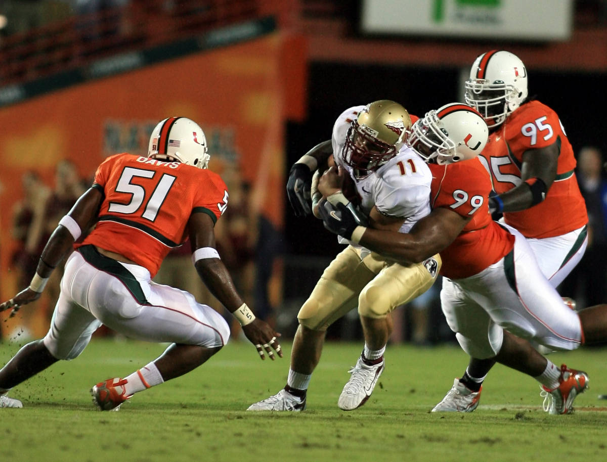 Florida State quarterback Drew Weatherford (11) is sacked by Miami defensive tackle Kareem Brown (99) as Romeo Davis (51) and Bryan Pata (95) come in during the first quarter Monday, Sept. 4, 2006 at the Orange Bowl in Miami. (AP Photo/Luis M. Alvarez)