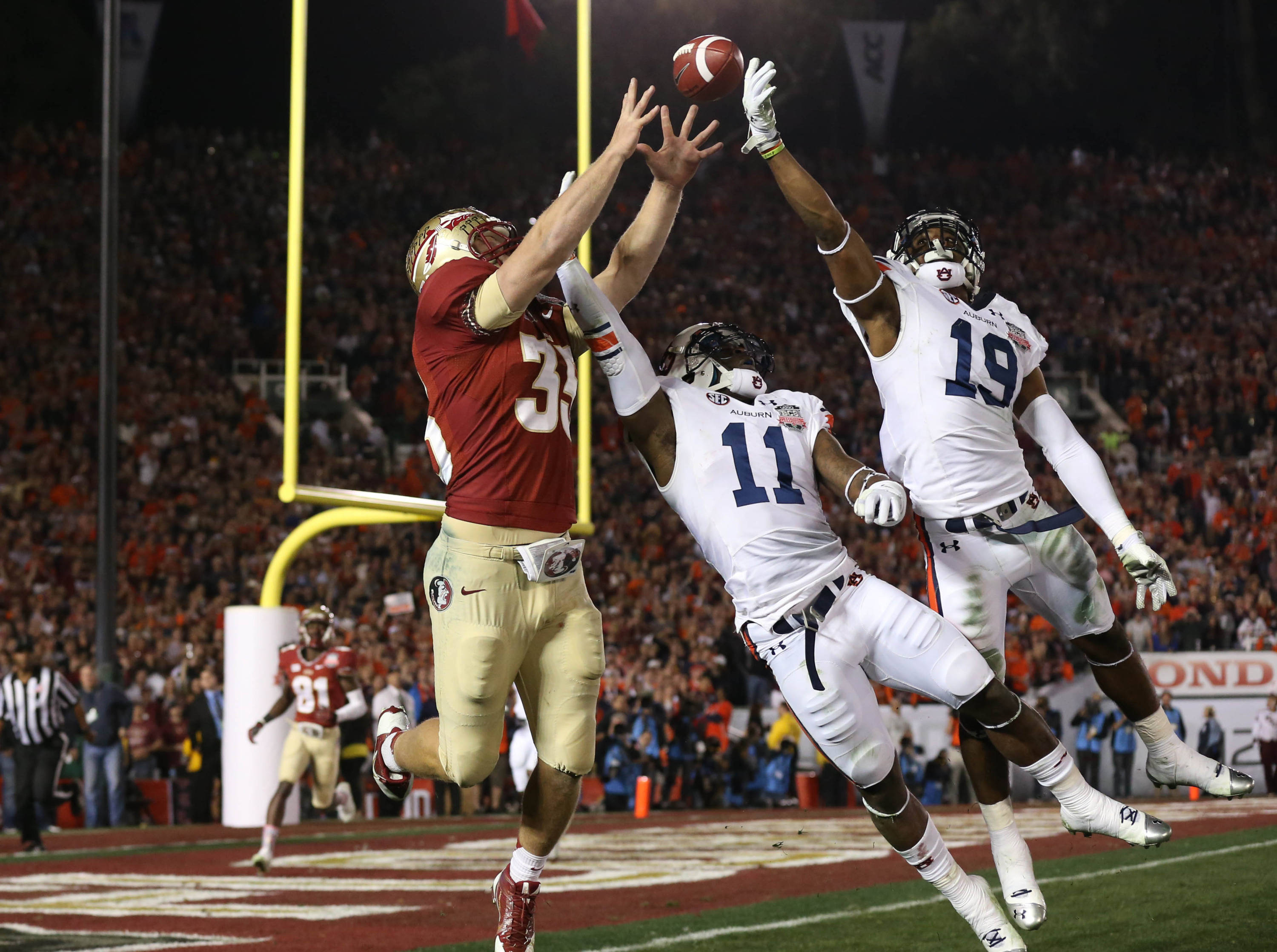 Jan 6, 2014; Pasadena, CA, USA; Auburn Tigers cornerback Chris Davis (11) and Ryan White  (19) break up a pass for Florida State Seminoles tight end Nick O'Leary (35) during the first half of the 2014 BCS National Championship game at the Rose Bowl.  Mandatory Credit: Matthew Emmons-USA TODAY Sports