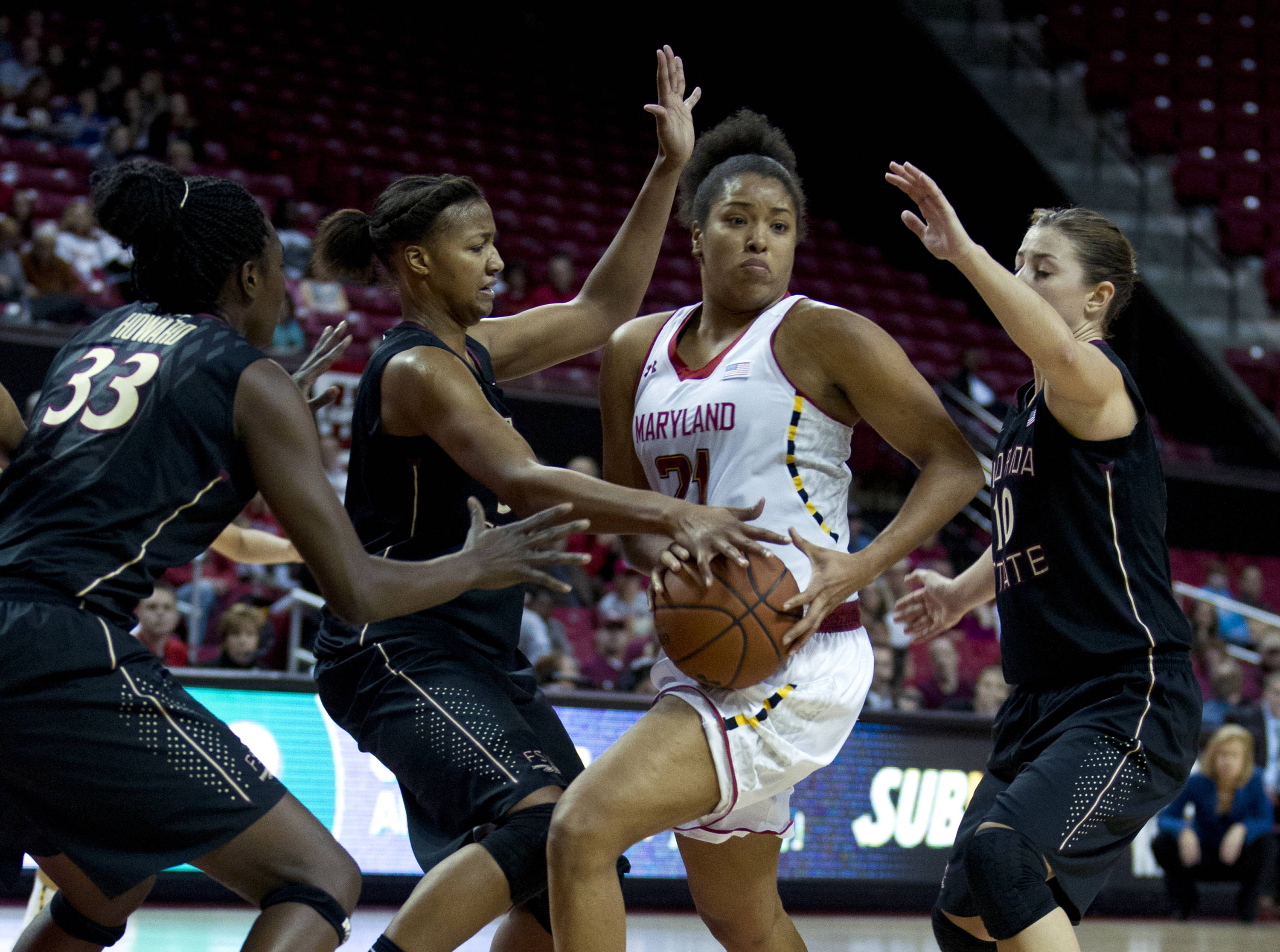 Maryland's Tianna Hawkins (21) moves the ball against Florida State's Natasha Howard (33), Chelsea Davis (34) and Leonor Rodriguez (10) who try to block during the second half. (AP Photo/Jose Luis Magana)