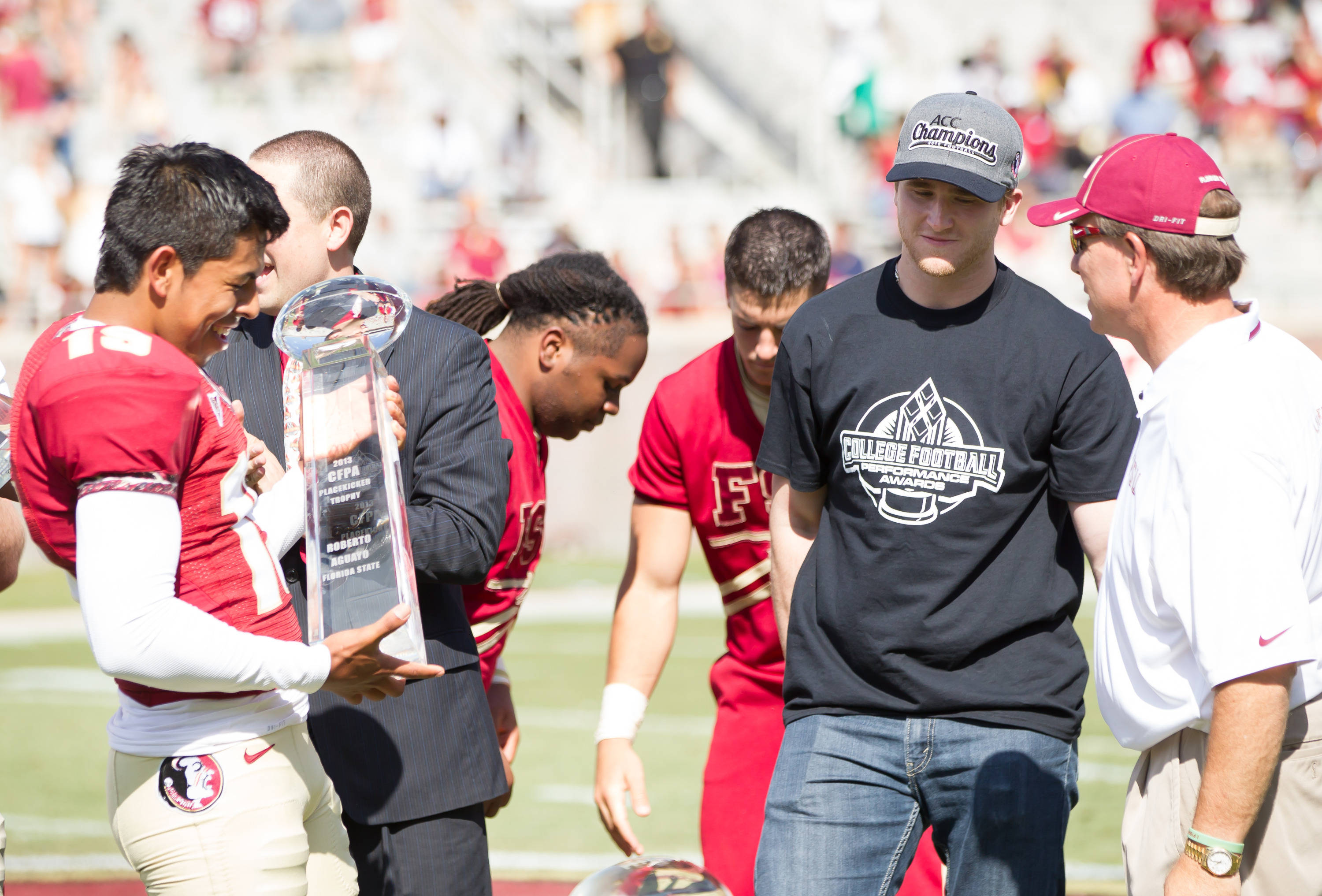 Roberto Aguayo (19) receives a national kicking award from Jimbo Fisher and Dustin Hopkins.