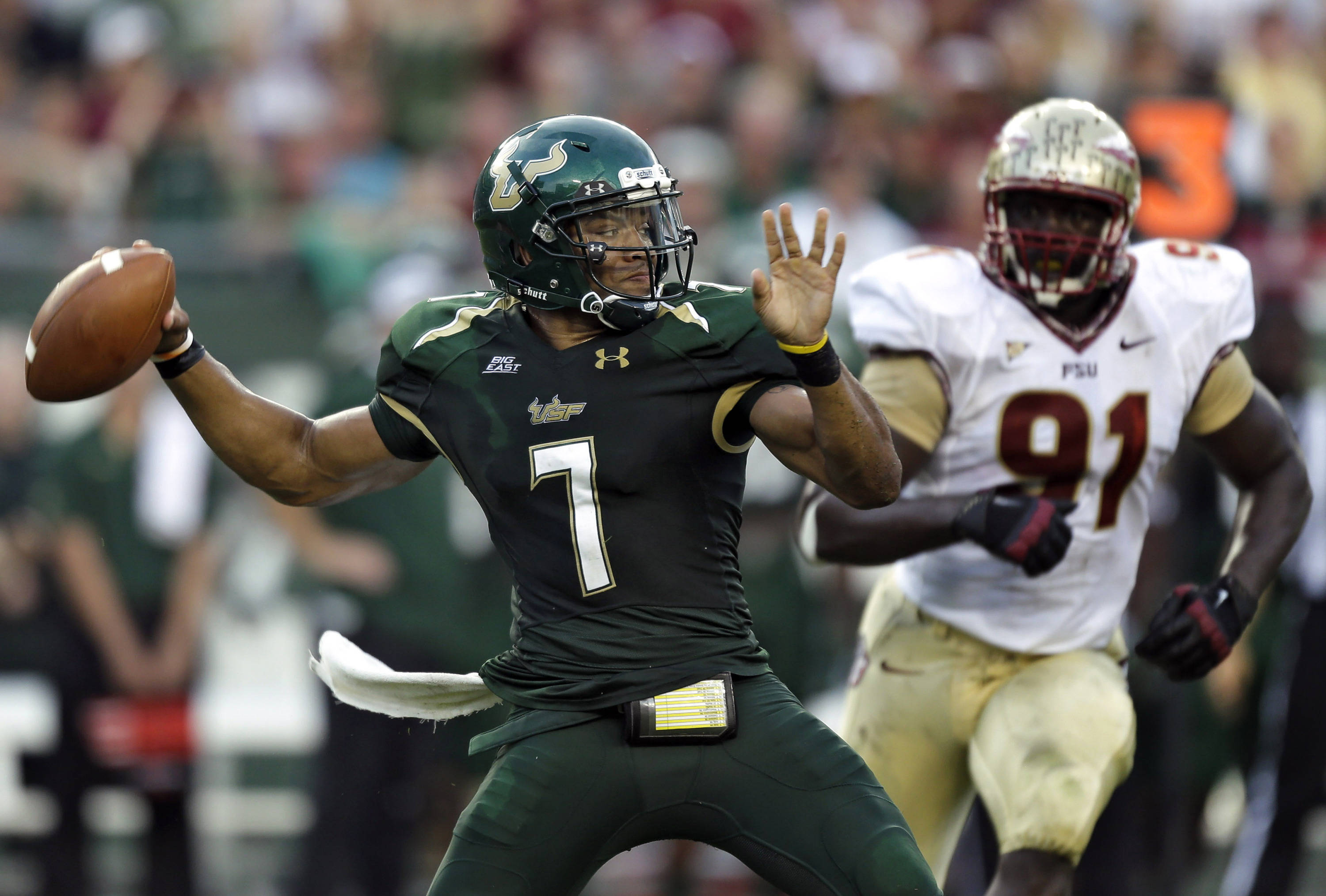 South Florida quarterback B.J. Daniels (7) fires a pass as he is pressured by Florida State defensive end Cornellius Carradine (91) during the first quarter. (AP Photo/Chris O'Meara)