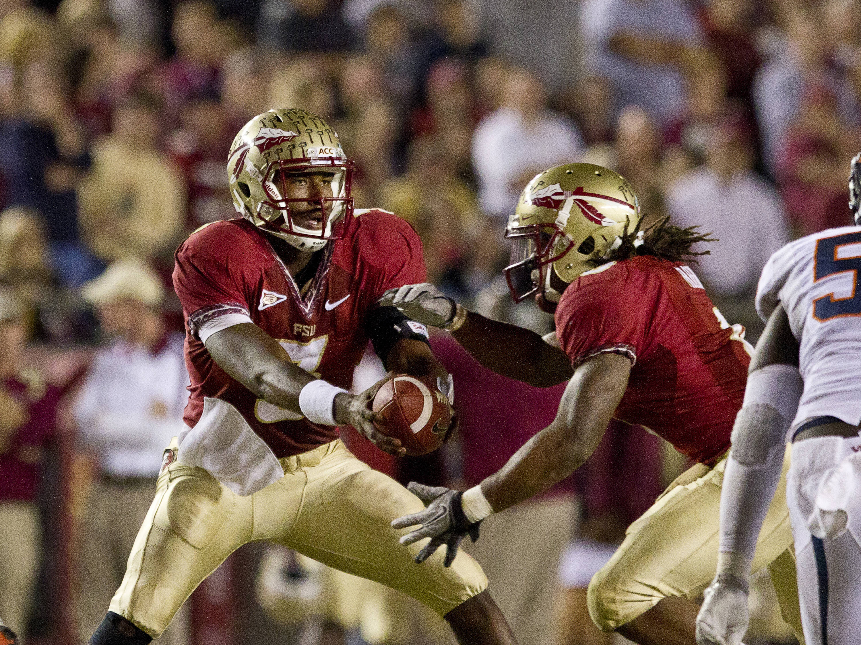 EJ Manuel (3) hands the ball off to Timmy Jernigan (8) during the game against Virginia on November 19, 2011.