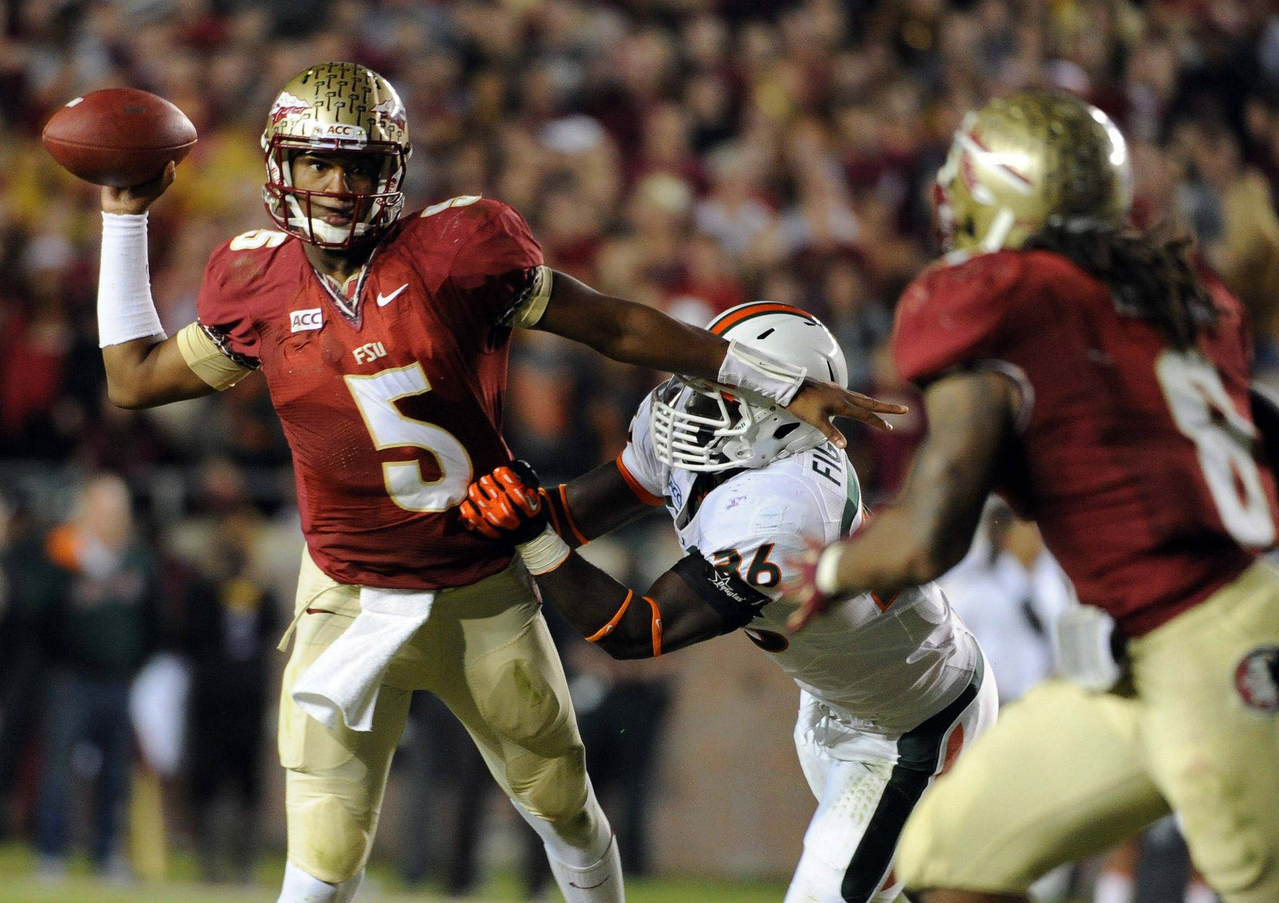 Florida State Seminoles quarterback Jameis Winston (5) evades Miami Hurricanes linebacker Alex Figueroa (36) as he throws the ball during the second half at Doak Campbell Stadium. Mandatory Credit: Melina Vastola-USA TODAY Sports