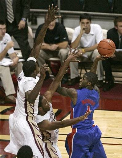 Florida's Kenny Boynton attempts a shot past the defense of Florida State's Michael Snaer and Bernard James, left. (AP Photo/Steve Cannon)