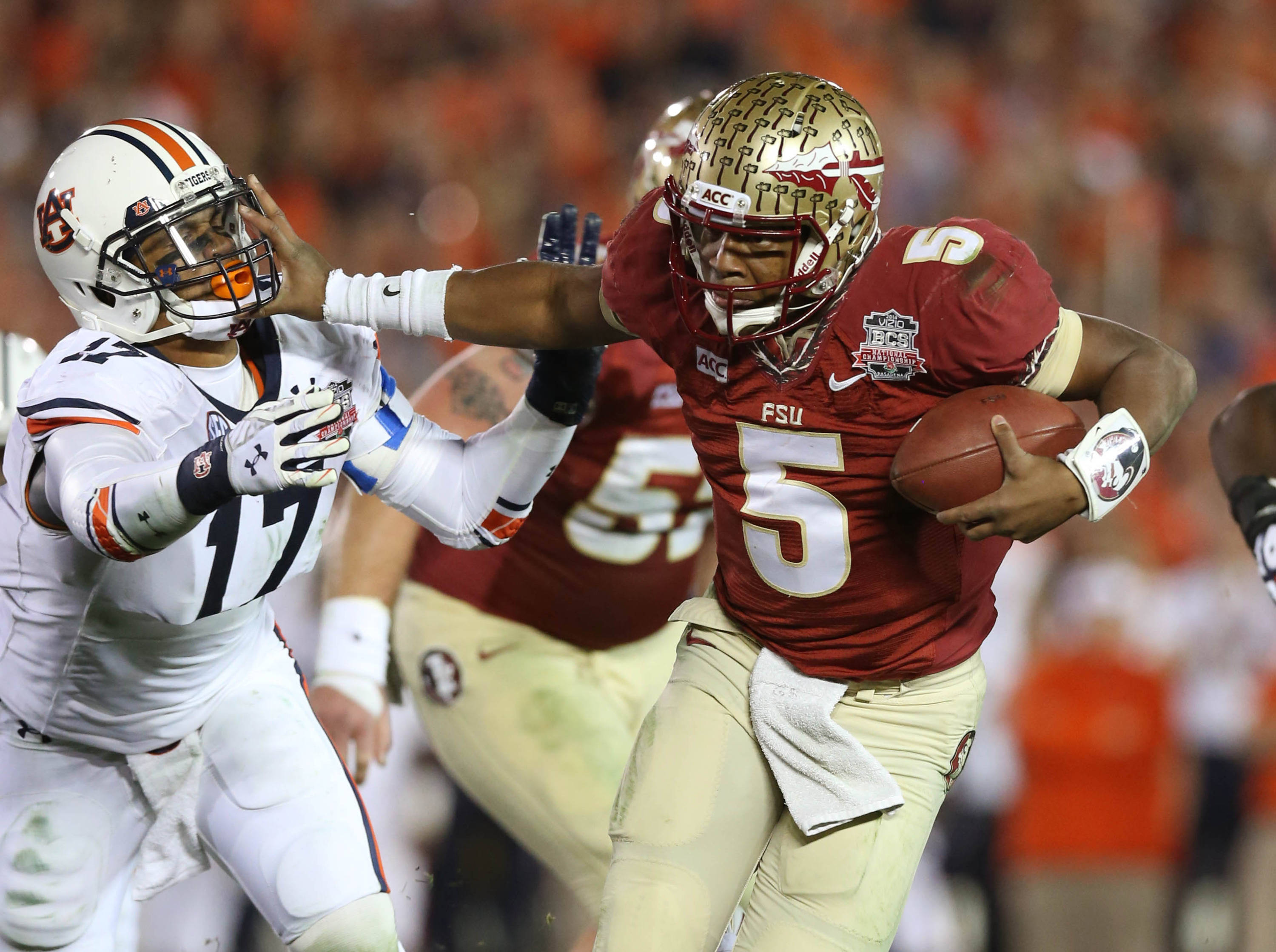 Jan 6, 2014; Pasadena, CA, USA; Florida State Seminoles quarterback Jameis Winston (5) stiff arms Auburn Tigers linebacker Kris Frost (17) during the first half of the 2014 BCS National Championship game at the Rose Bowl.  Mandatory Credit: Matthew Emmons-USA TODAY Sports