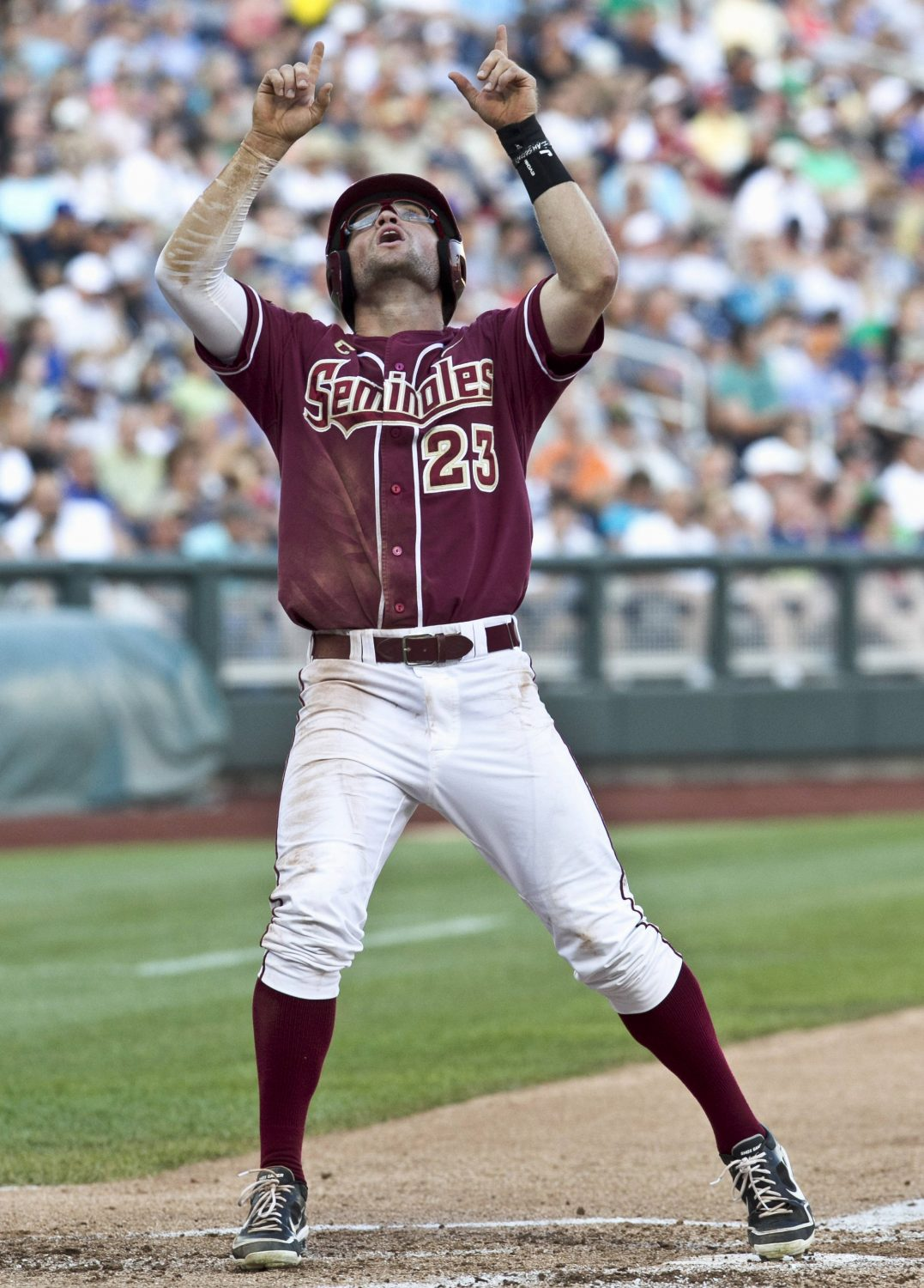 Florida State's James Ramsey points skyward at home plate as he scores against UCLA after Justin Gonzalez was walked with bases loaded in the first inning. (AP Photo/Nati Harnik)