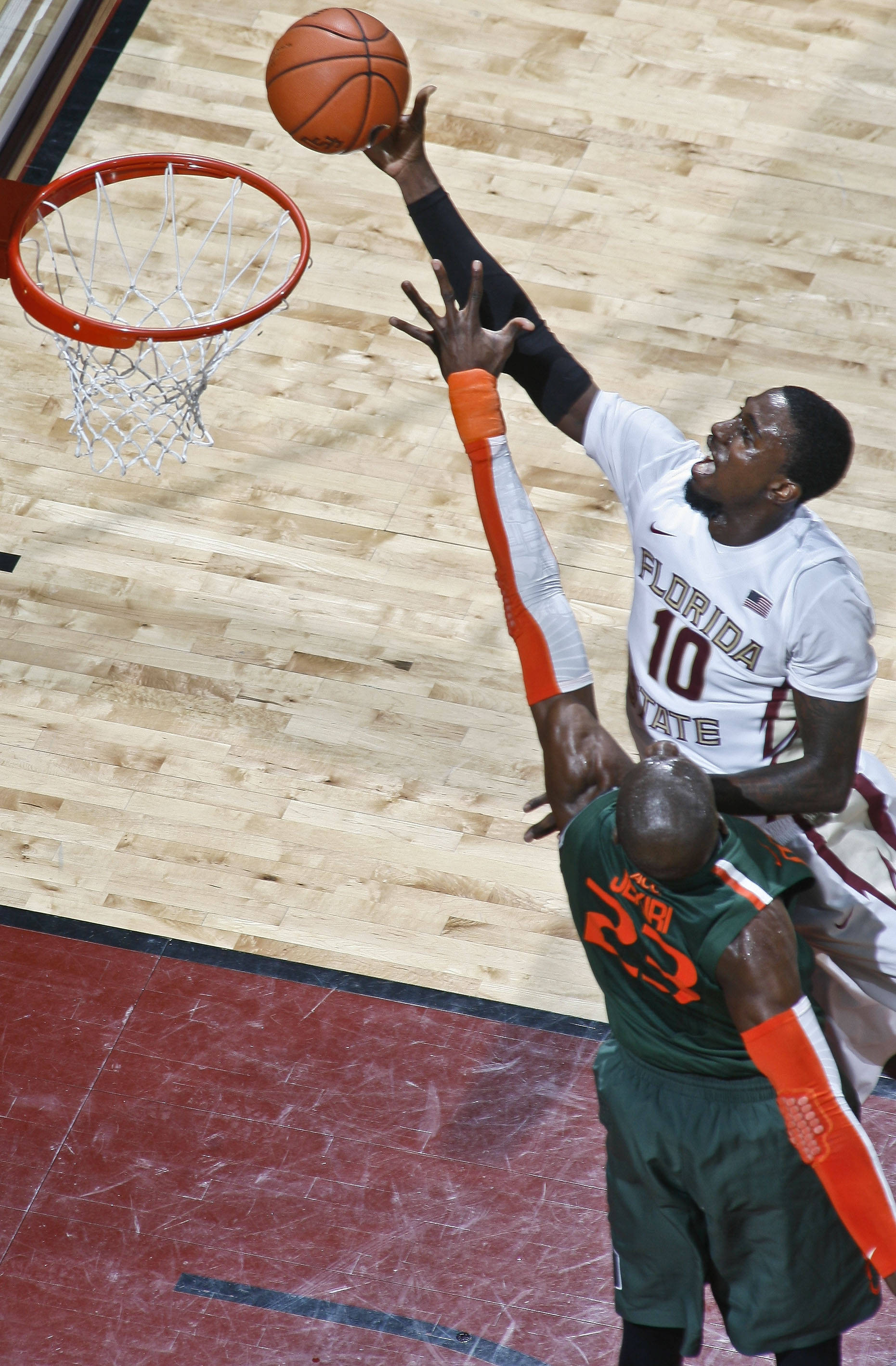 Feb 10, 2014; Tallahassee, FL, USA; Seminoles forward Okaro White (10) makes a layup over the defense of Miami Hurricanes center Tonye Jekiri (23) in the first half. Phil Sears-USA TODAY Sports