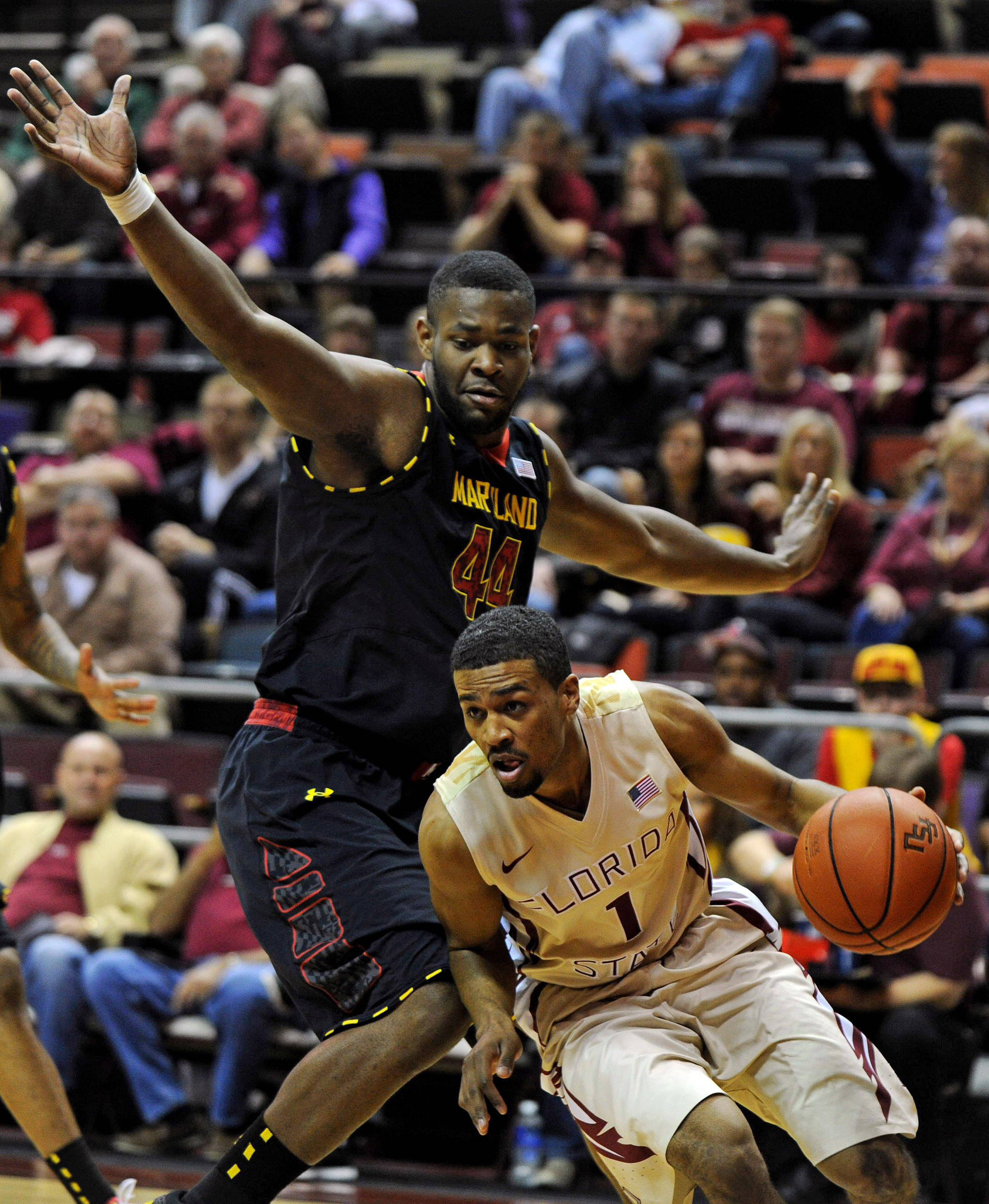 Jan 12, 2014; Tallahassee, FL, USA; Florida State Seminoles guard Devon Bookert (1) moves the ball past Maryland Terrapins center Shaquille Cleare (44) during the first half at Donald L. Tucker Center. Mandatory Credit: Melina Vastola-USA TODAY Sports
