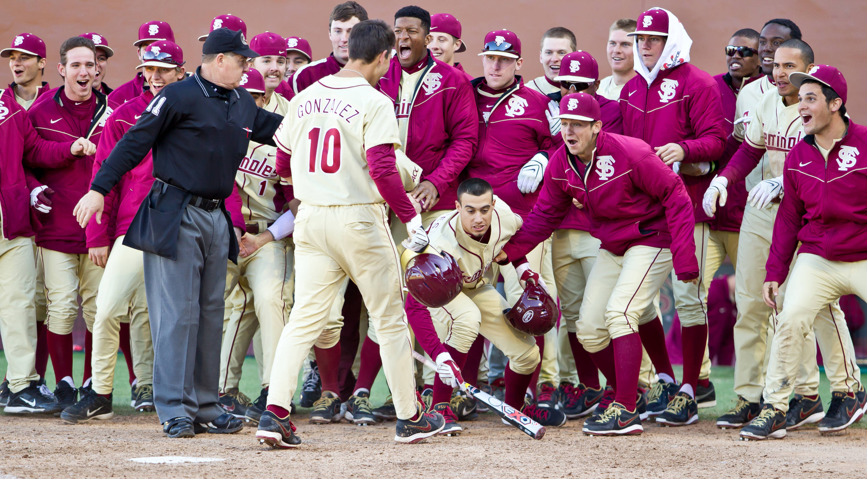 The Seminoles celebrate at the plate following FSU's victory over Rhode Island on Sunday.