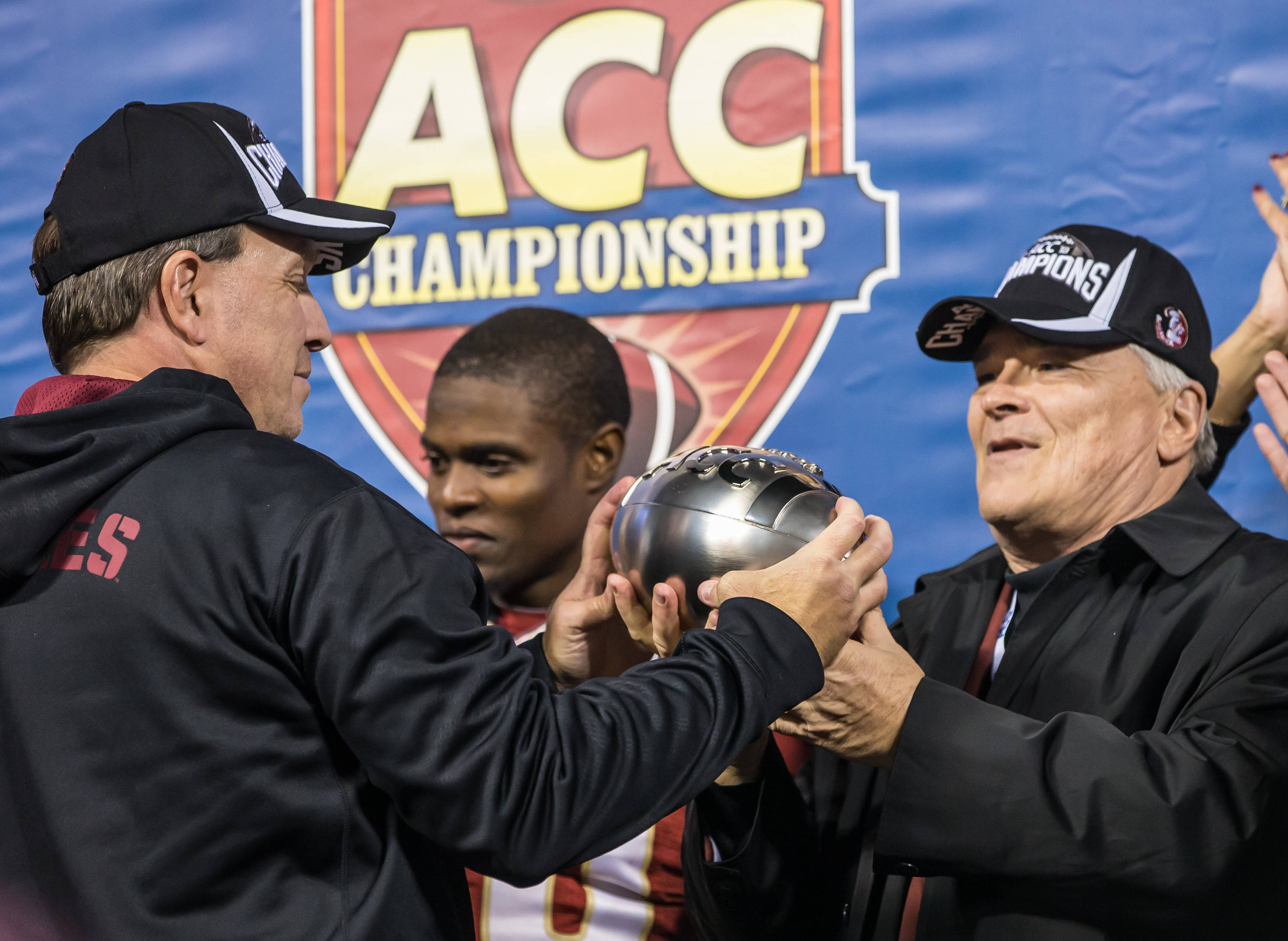 Jimbo Fisher hands off the ACC Championship Trophy to FSU President Eric Barron.