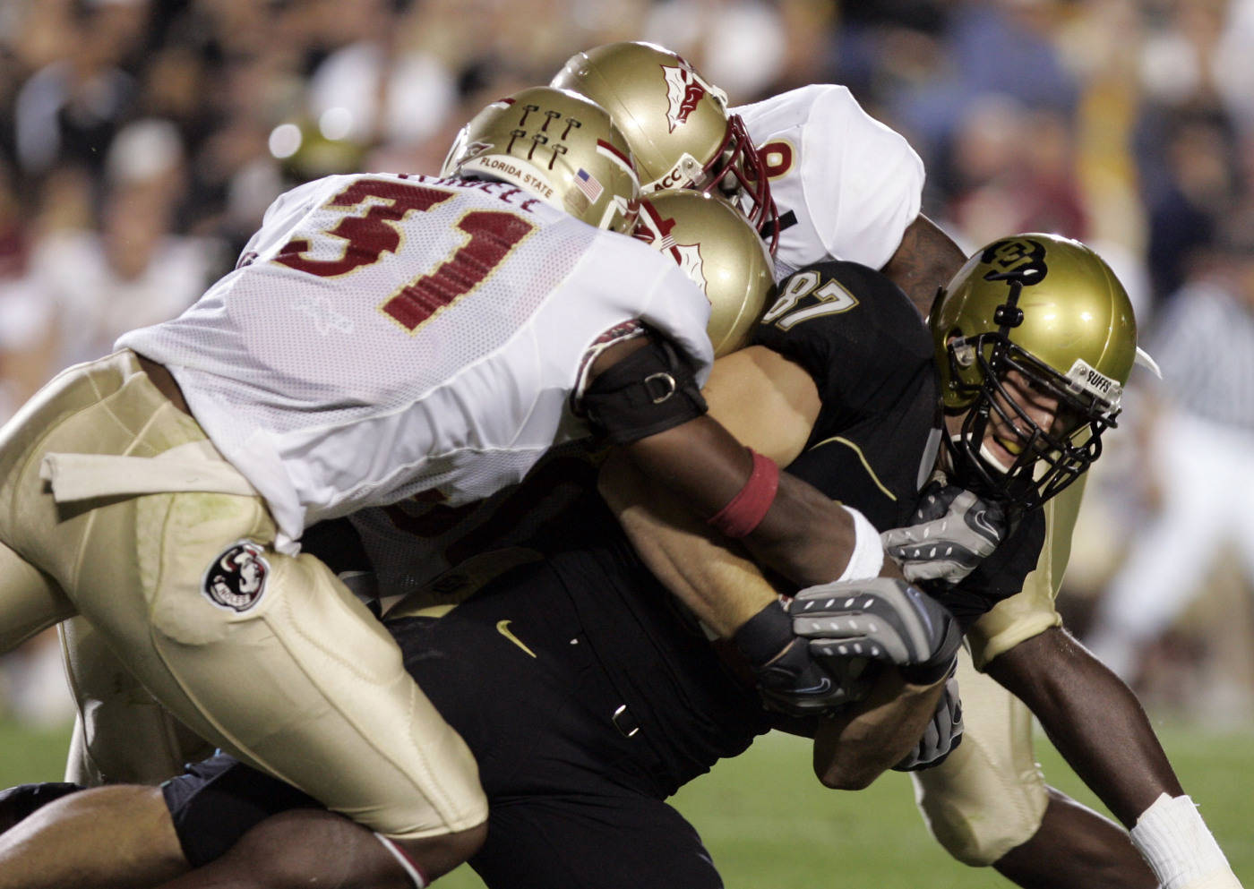 Colorado tight end Riar Geer, right, is tackled after catching a pass by Florida State defenders, from left front to back, Toddrick Verdell, Derek Nicholson and J.R. Bryant in the second quarter. (AP Photo/Jack Dempsey)[