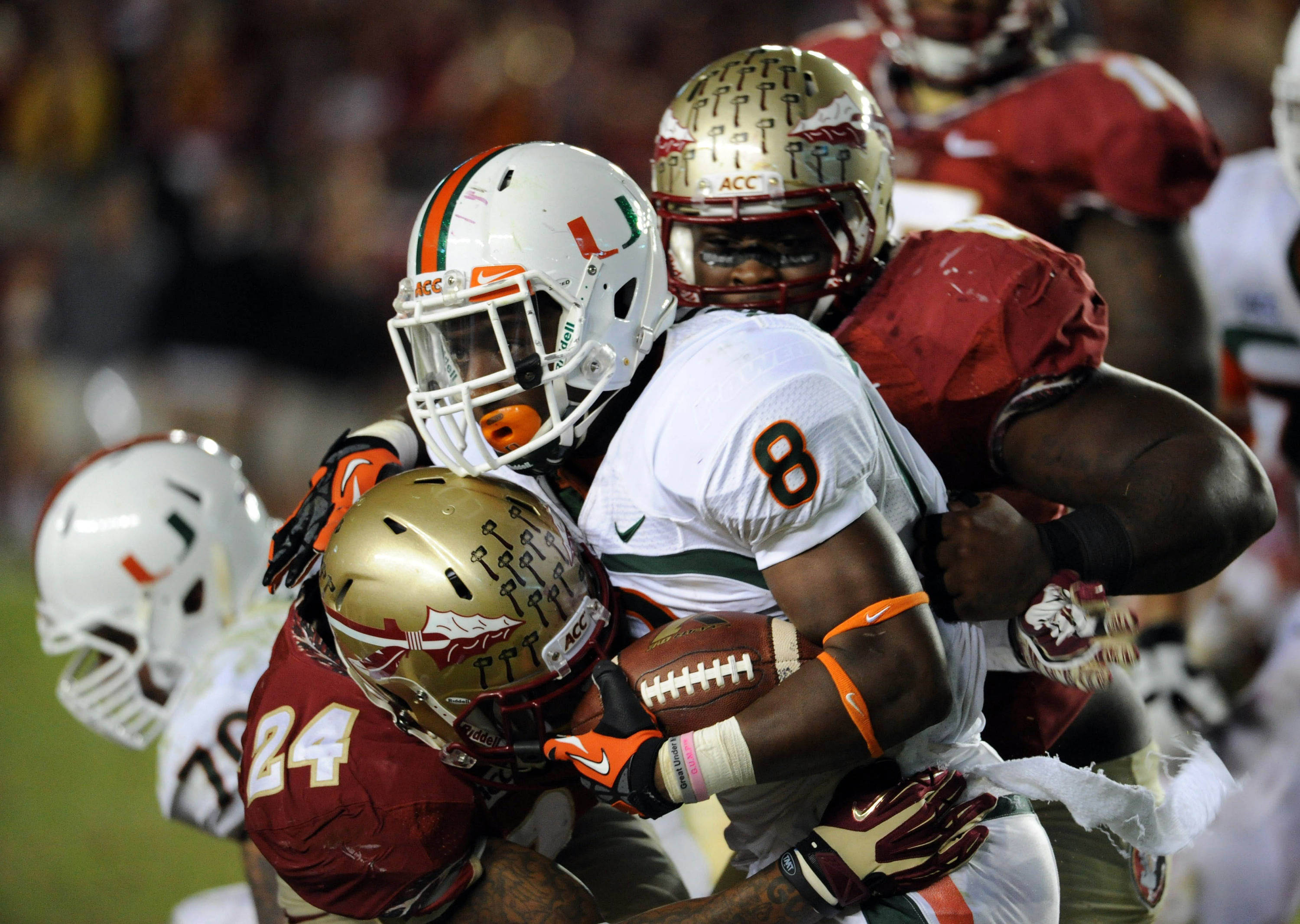 Miami Hurricanes running back Duke Johnson (8) is tackled by Florida State Seminoles linebacker Terrance Smith (24) and defensive tackle Timmy Jernigan (8) during the first half at Doak Campbell Stadium. Mandatory Credit: Melina Vastola-USA TODAY Sports