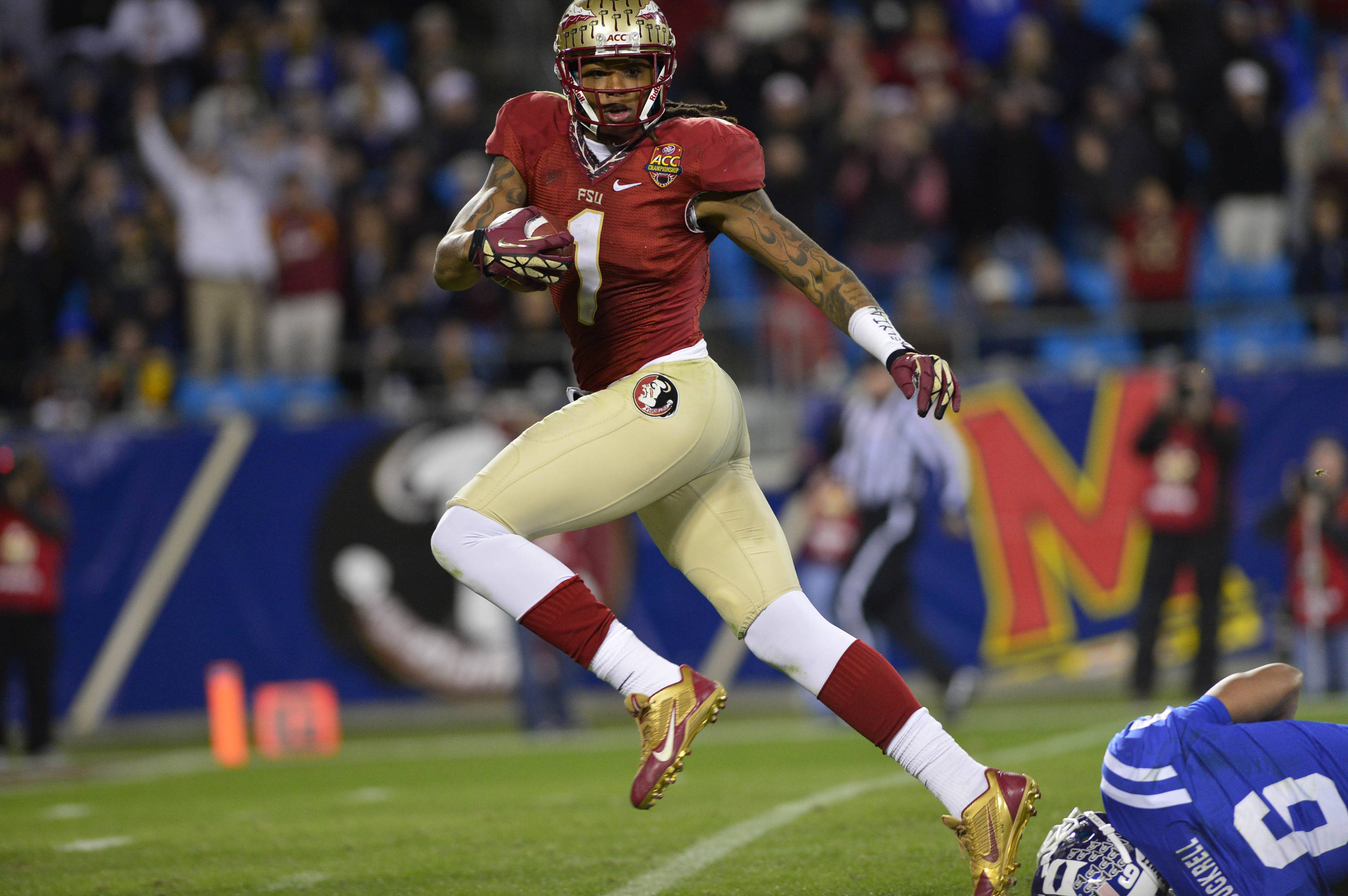 Dec 7, 2013; Charlotte, NC, USA; Florida State Seminoles wide receiver Kelvin Benjamin (1) breaks free from Duke Blue Devils cornerback Ross Cockrell (6) and scores a touchdown in the third quarter at Bank of America Stadium. Mandatory Credit: Bob Donnan-USA TODAY Sports