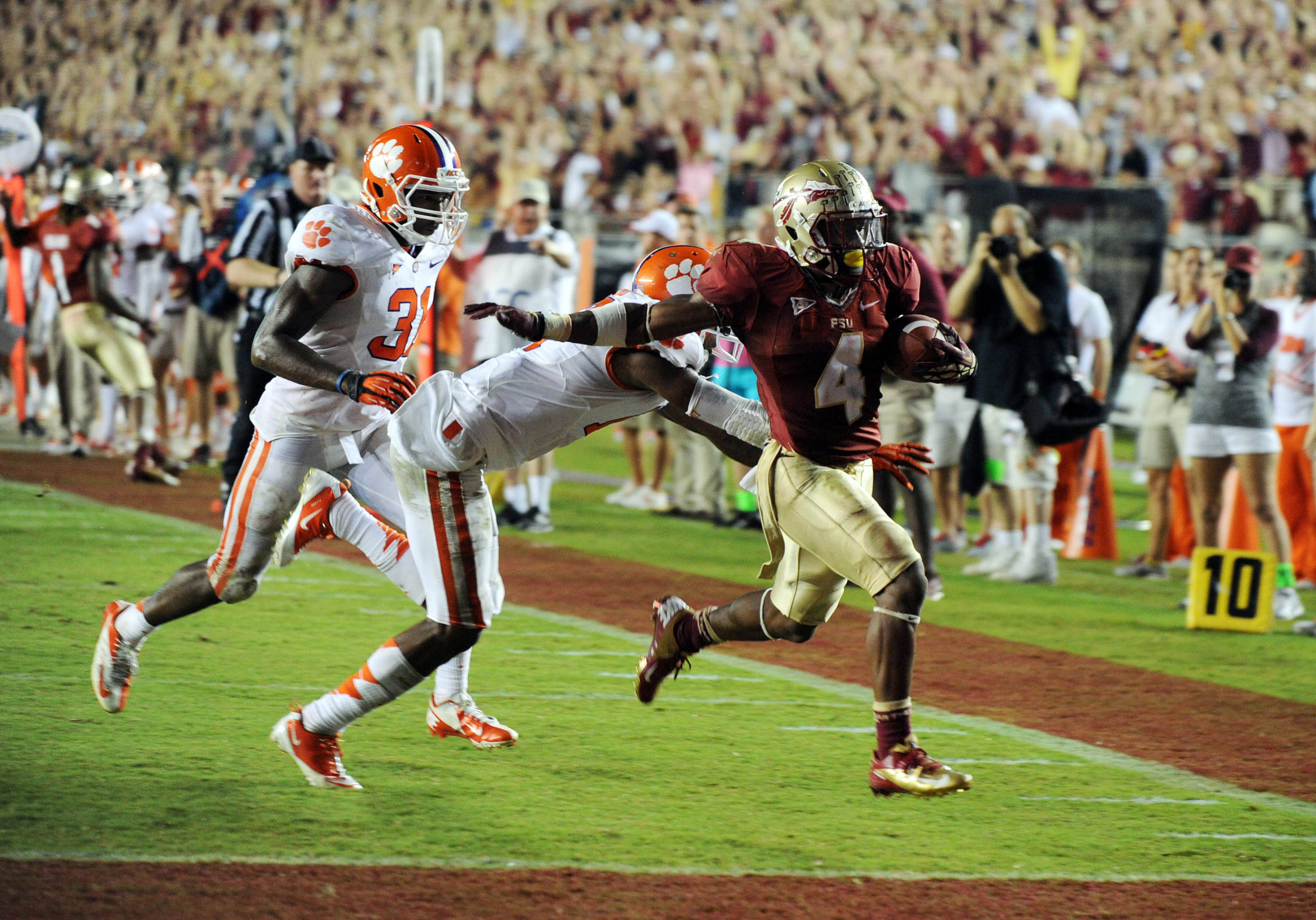 Sept 22, 2012;  Tallahassee, Florida, USA; Florida State Seminoles running back Chris Thompson (4) runs for a touchdown past Clemson Tigers cornerback Bashaud Breeland (17) and safety Rashard Hall (31) during the second half of the game at Doak Campbell Stadium. Mandatory Credit: Melina Vastola-USA TODAY Sports