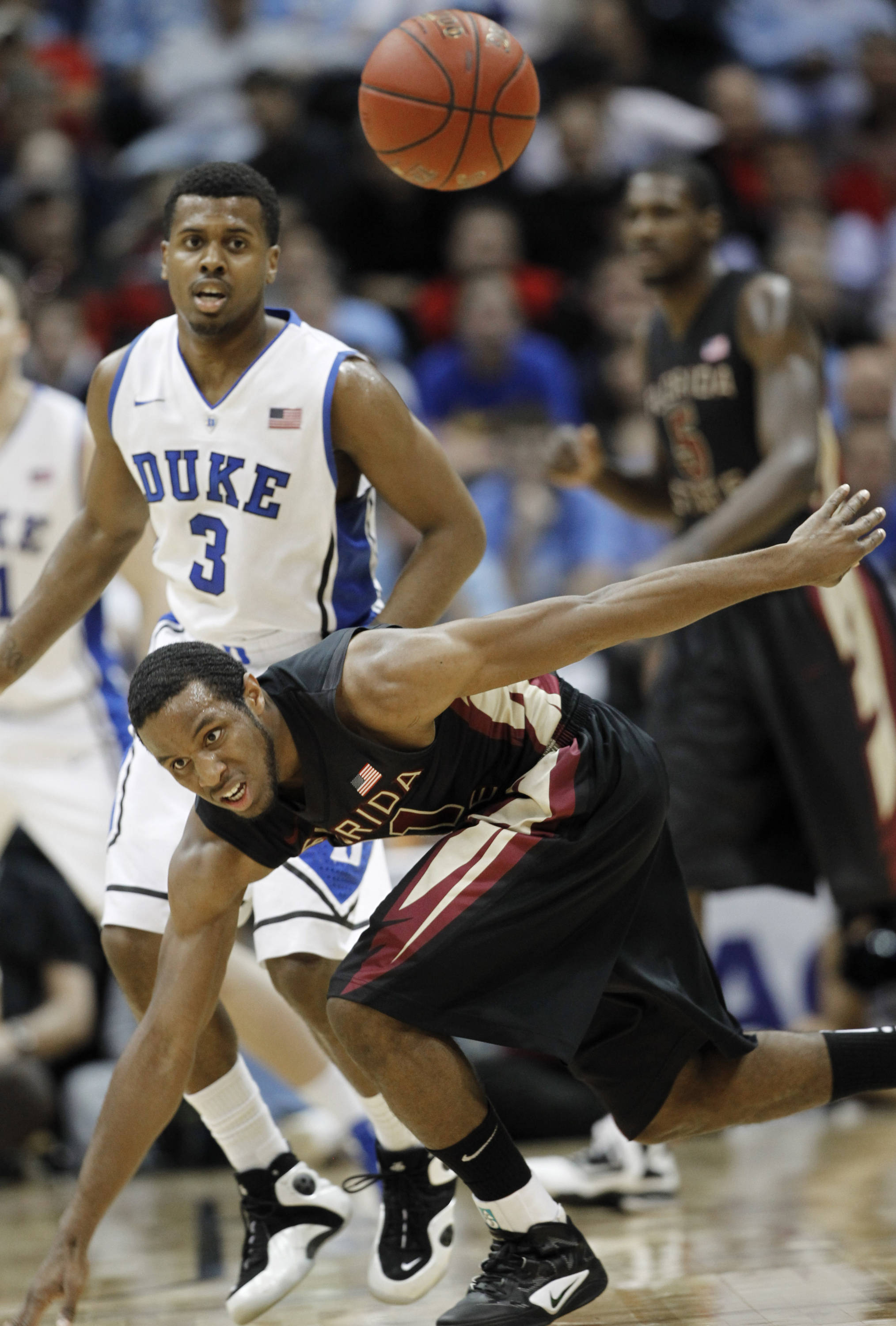 Florida State guard Michael Snaer (21) loses his footing as he tries to catch a loose ball with Duke guard Tyler Thornton (3) during the first half of an NCAA college basketball game in the semifinals of the Atlantic Coast Conference tournament, Saturday, March 10, 2012, in Atlanta. (AP Photo/John Bazemore)