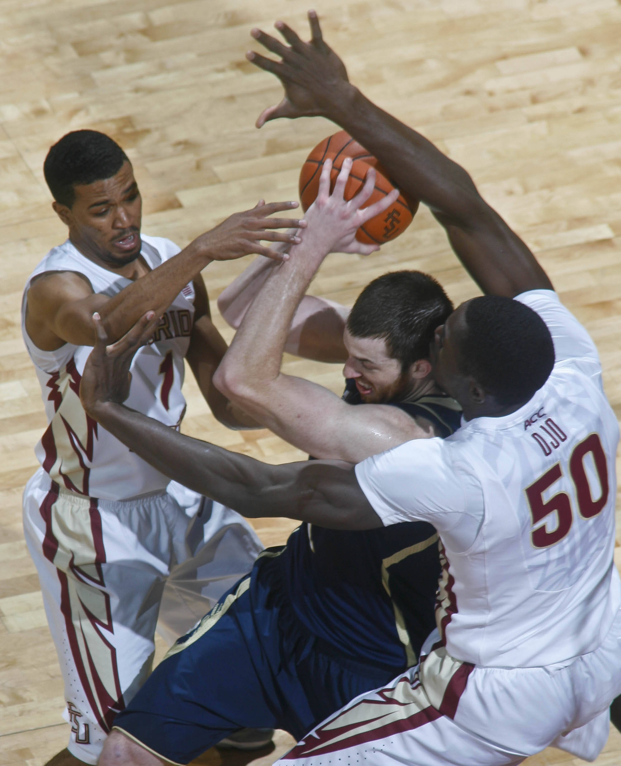 Jan 21, 2014; Tallahassee, FL, USA; Notre Dame Fighting Irish center Garrick Sherman (11) gets double-teamed by Florida State Seminoles guard Devon Bookert (1) and center Michael Ojo (50)in the first half at the Donald L. Tucker Center. Mandatory Credit: Phil Sears-USA TODAY Sports