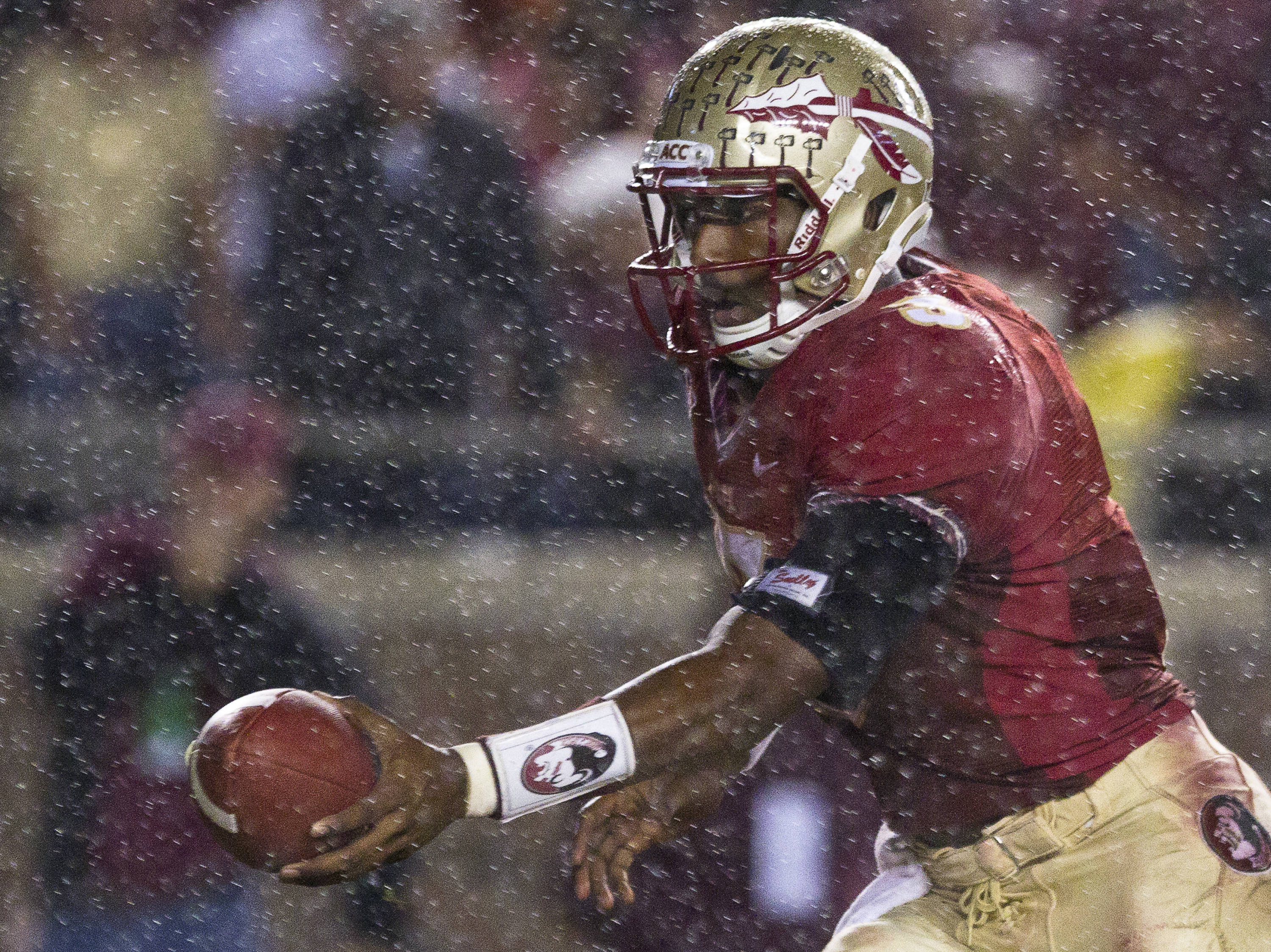 EJ Manuel (3) hands the ball off in the rain during the Virginia game