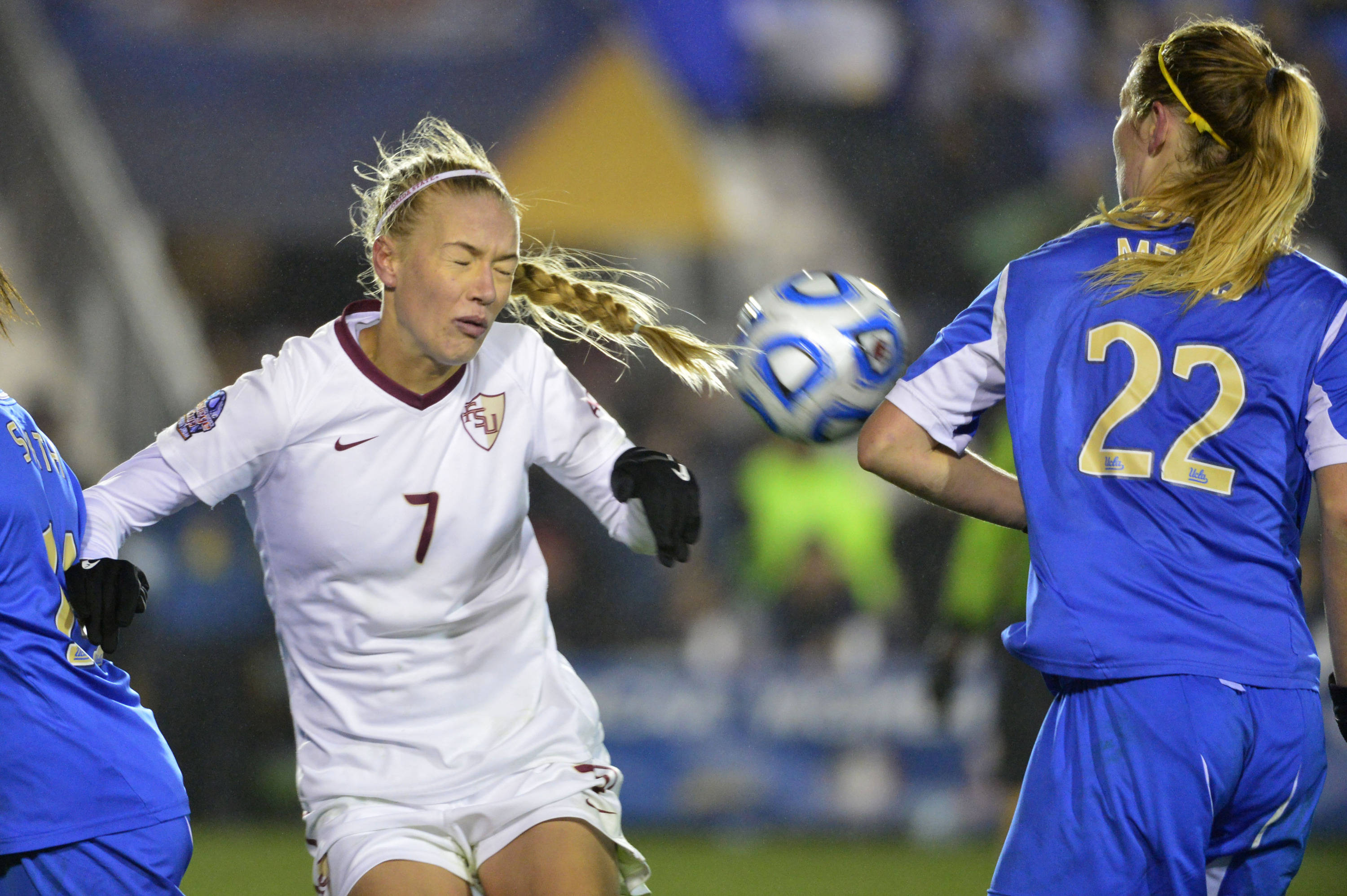 Dec 8, 2013; Cary, NC, USA; Florida State Seminoles midfielder Dagny Brynjarsdottir (7) heads the ball as UCLA Bruins forward Taylor Smith (14) and midfield/forward Sam Mewis (22) defend. The Bruins defeated the Seminoles 1-0 in overtime at WakeMed Soccer Park. Mandatory Credit: Bob Donnan-USA TODAY Sports