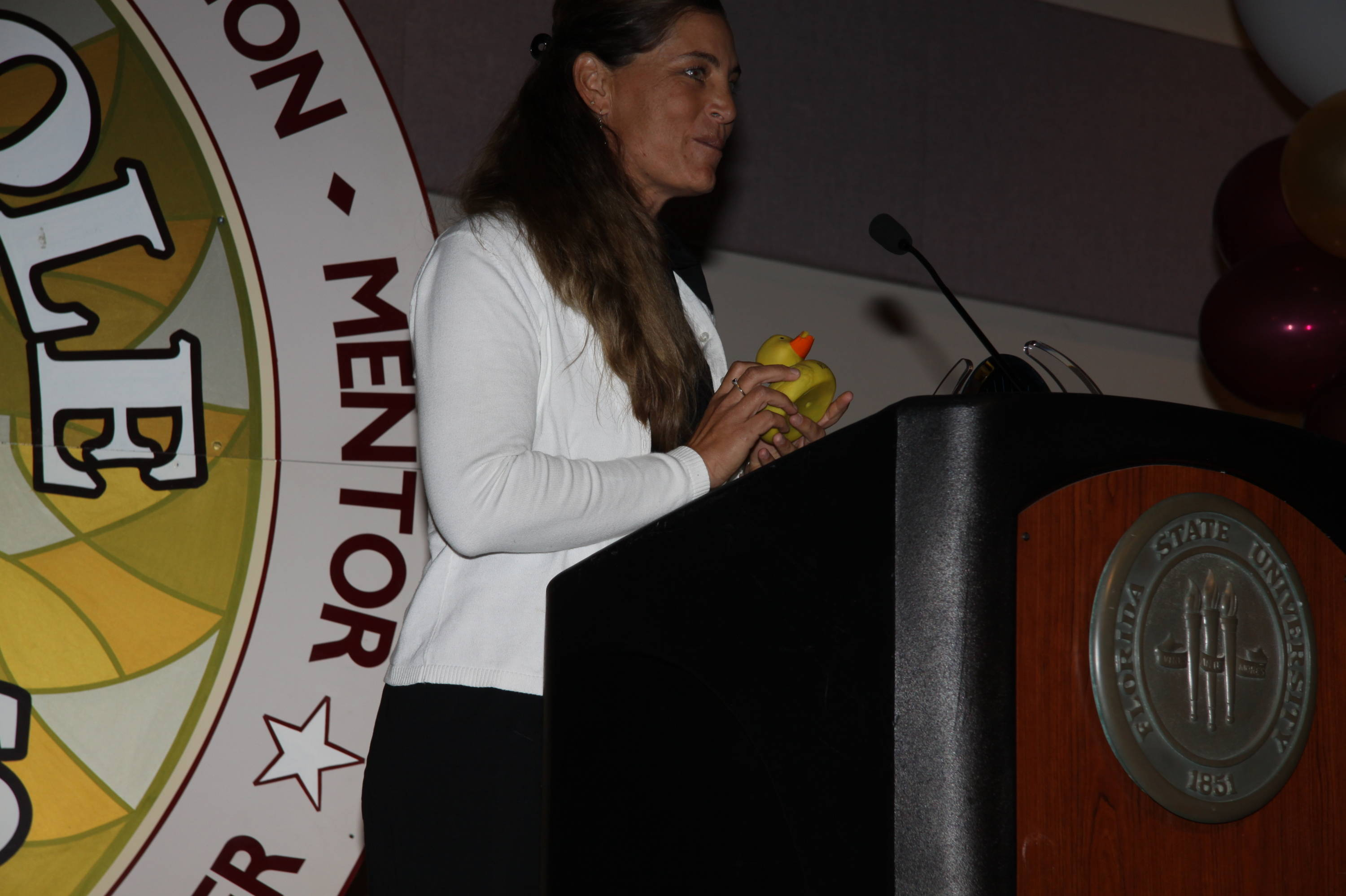 Head coach Lonni Alameda speaks at the podium of the Golden Nole Banquet