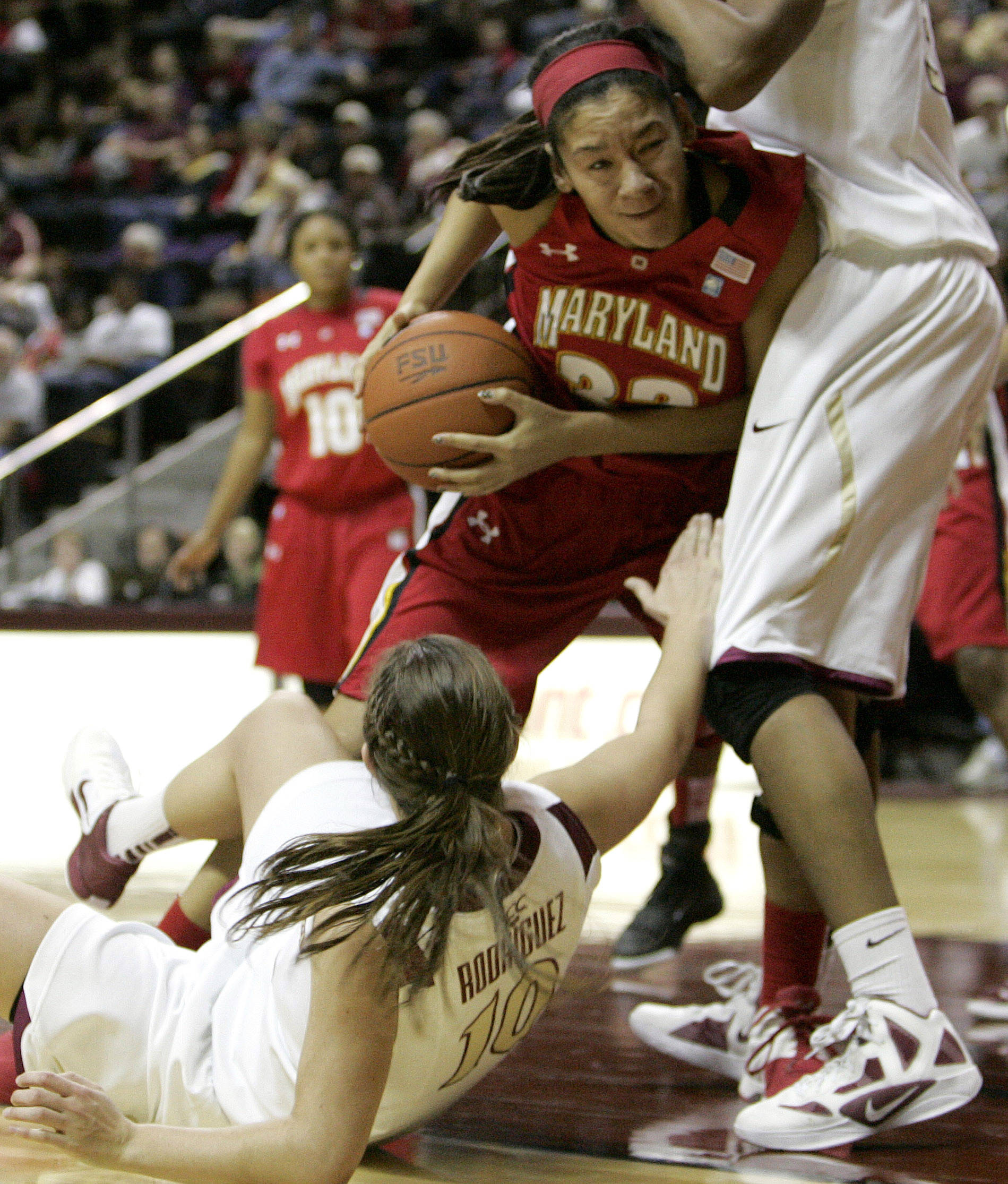 Maryland's Whitney Bays, center, drives against Florida State's Leonor Rodriguez, bottom, and Chelsea Davis, right, in the second half of an NCAA college basketball game on Monday, Jan. 2, 2012, in Tallahassee, Fla. Maryland won 91-70. (AP Photo/Steve Cannon)