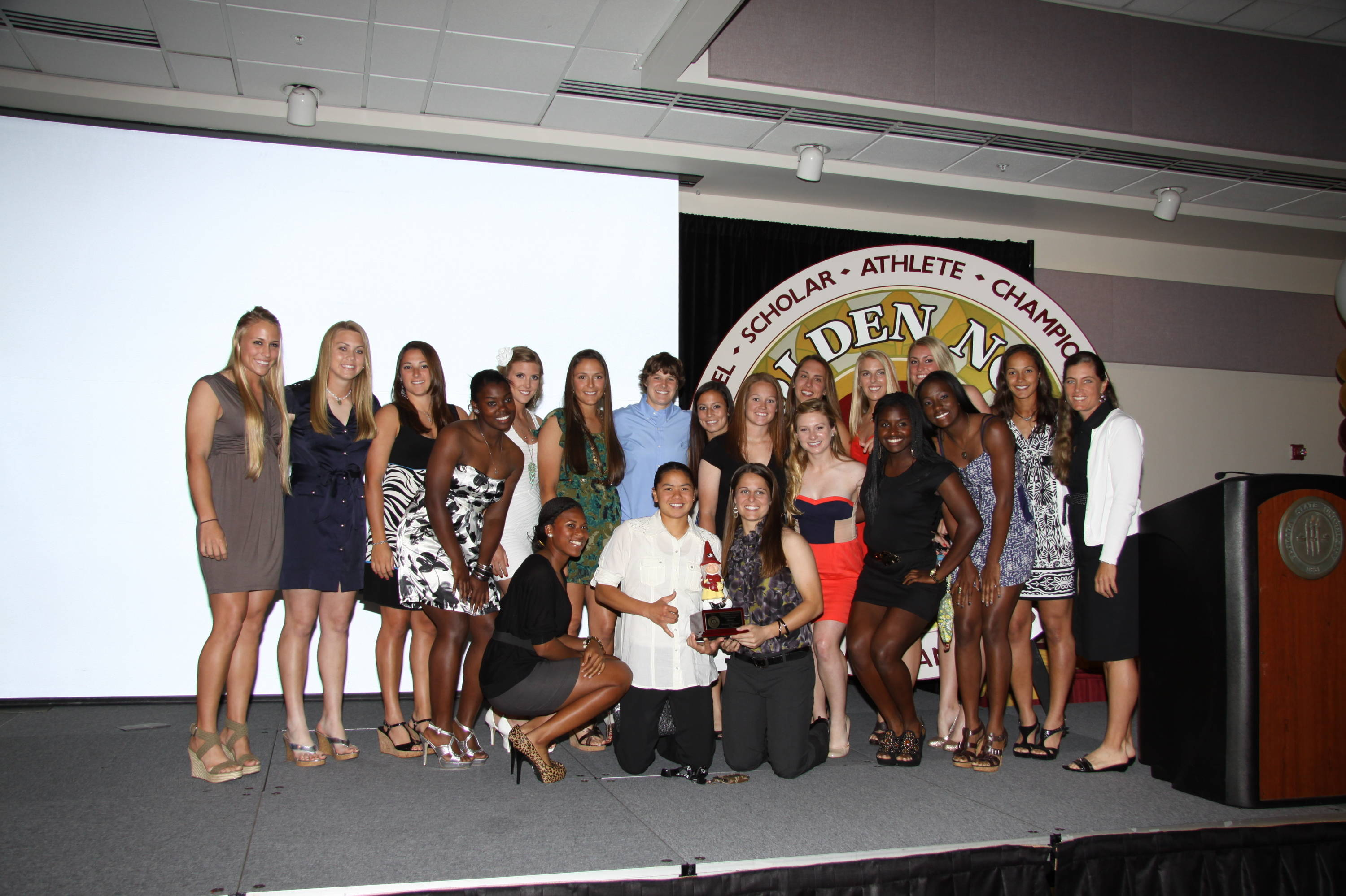 The 2011 softball team poses with its SemiGnome Award. Courtney Senas, who is kneeling in the middle next to the award, appears to be giving a shout-out to her native Hawaiians.