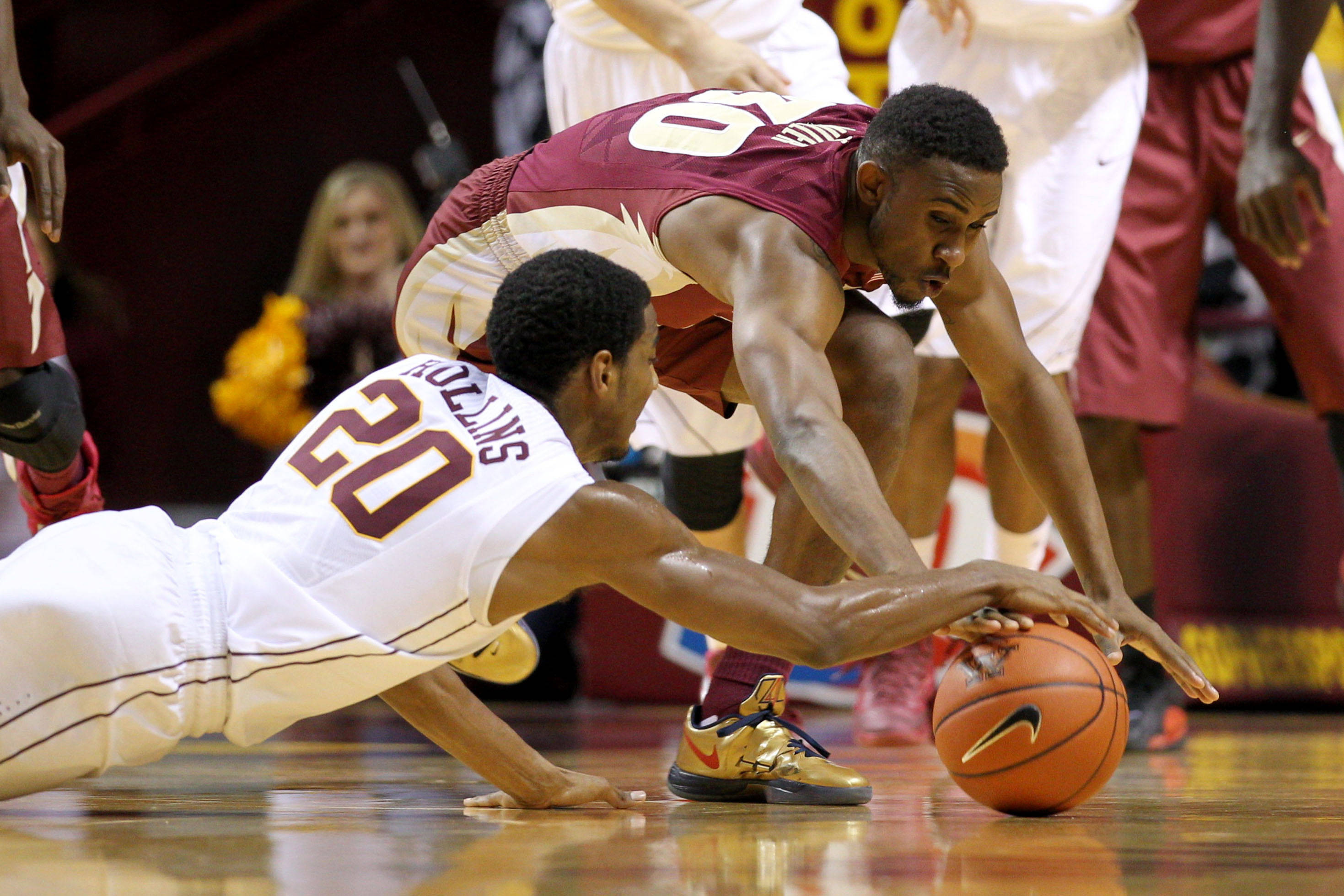 Dec 3, 2013; Minneapolis, MN, USA; Florida State Seminoles guard Ian Miller (30) and Minnesota Golden Gophers guard Austin Hollins (20) dive for the ball during the first half at Williams Arena. Mandatory Credit: Brace Hemmelgarn-USA TODAY Sports