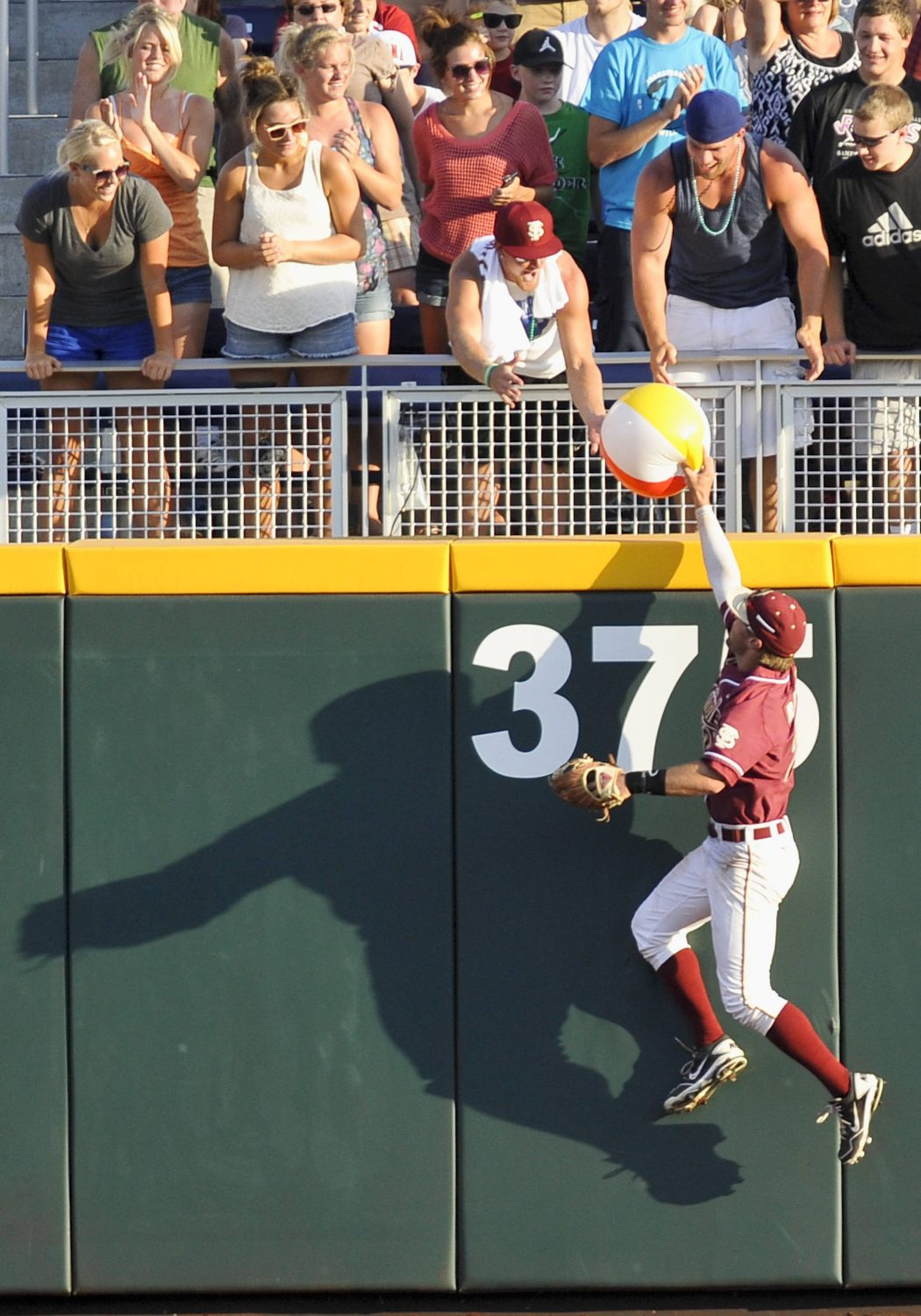 Florida State center fielder James Ramsey finds time to return a beach ball to the stands in the second inning. (AP Photo/Eric Francis)