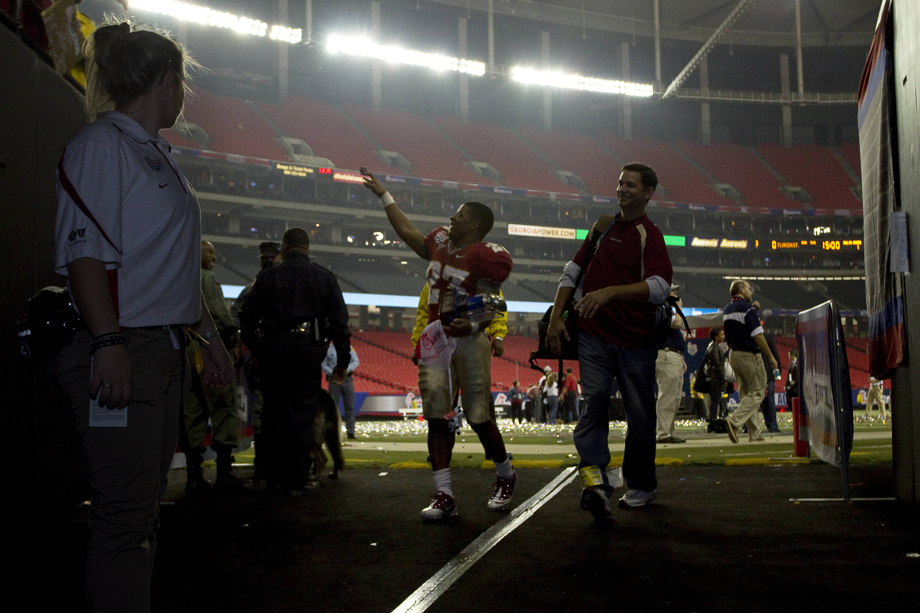 Chris Thompson (23) waves to cheering fans as he leaves the field after the Chick-fil-a Bowl
