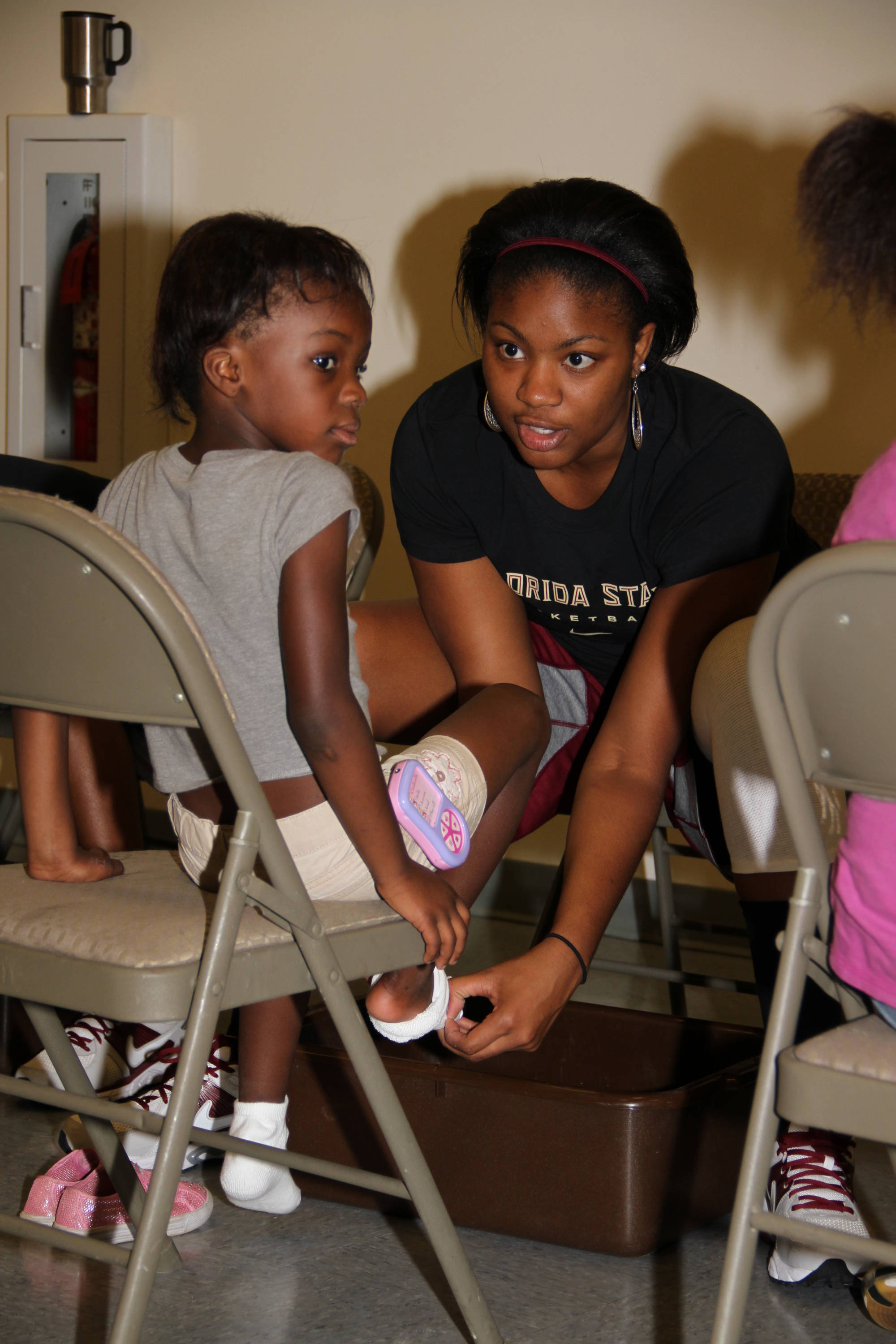 Women's Basketball Community Service: A shoe fitting at Springfield Community Center on Joe Louis Street.