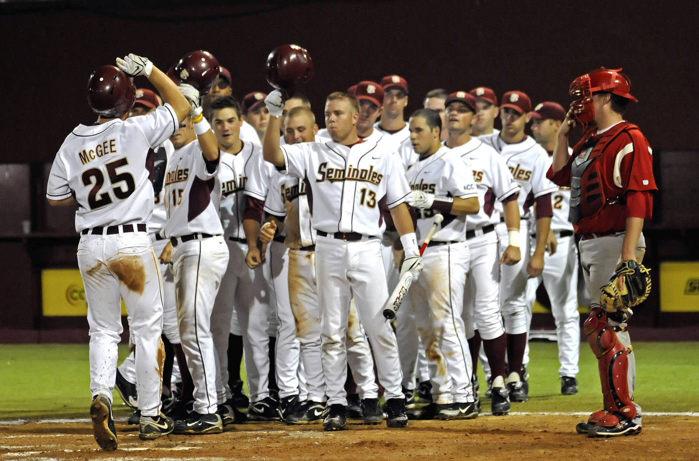 The Seminoles celebrate at the plate after Mike McGee's home run.