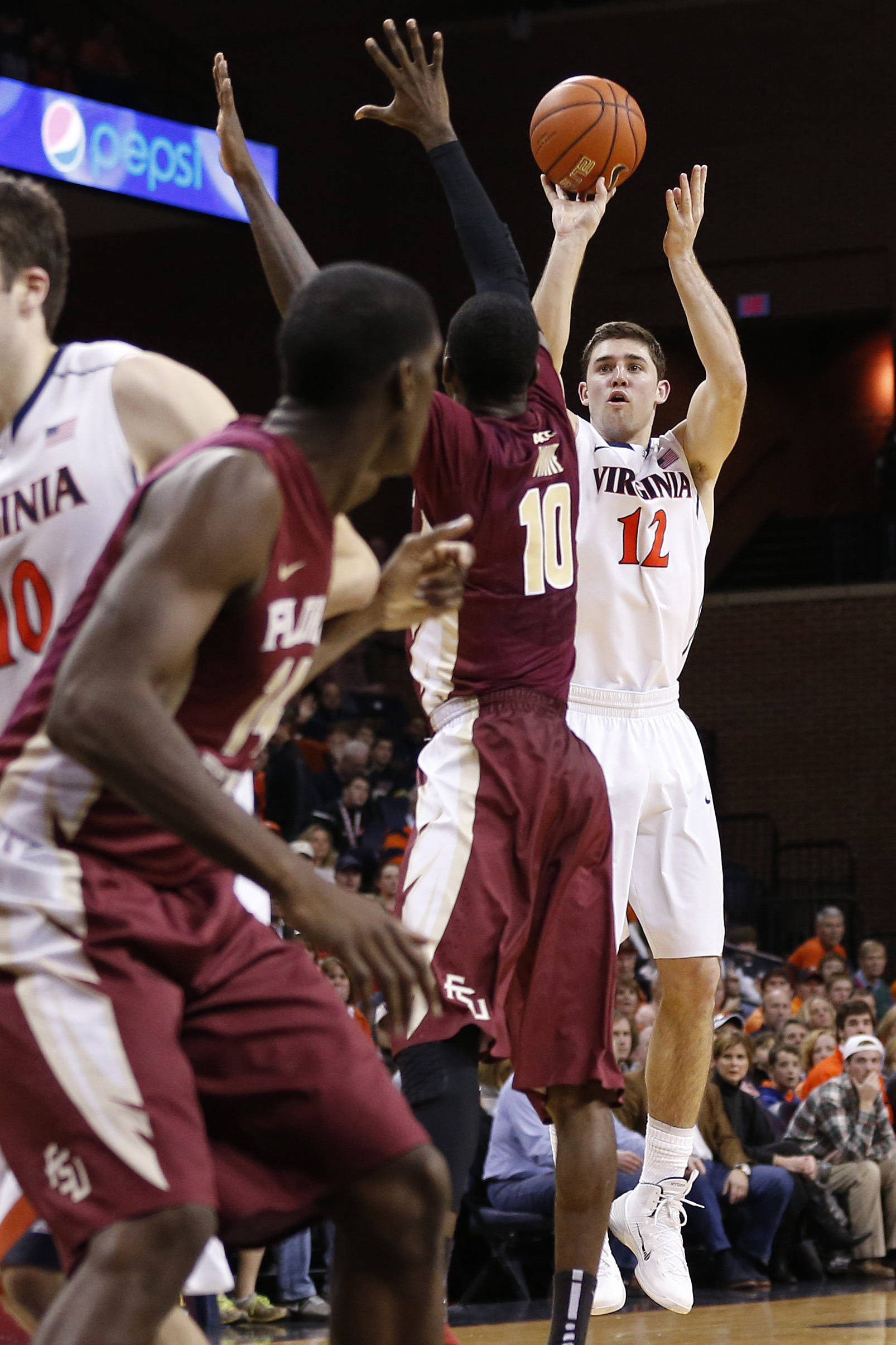 Jan 18, 2014; Charlottesville, VA, USA; Virginia Cavaliers guard Joe Harris (12) shoots the ball over Florida State Seminoles forward Okaro White (10) in the second half at John Paul Jones Arena. The Cavaliers won 78-66. Mandatory Credit: Geoff Burke-USA TODAY Sports